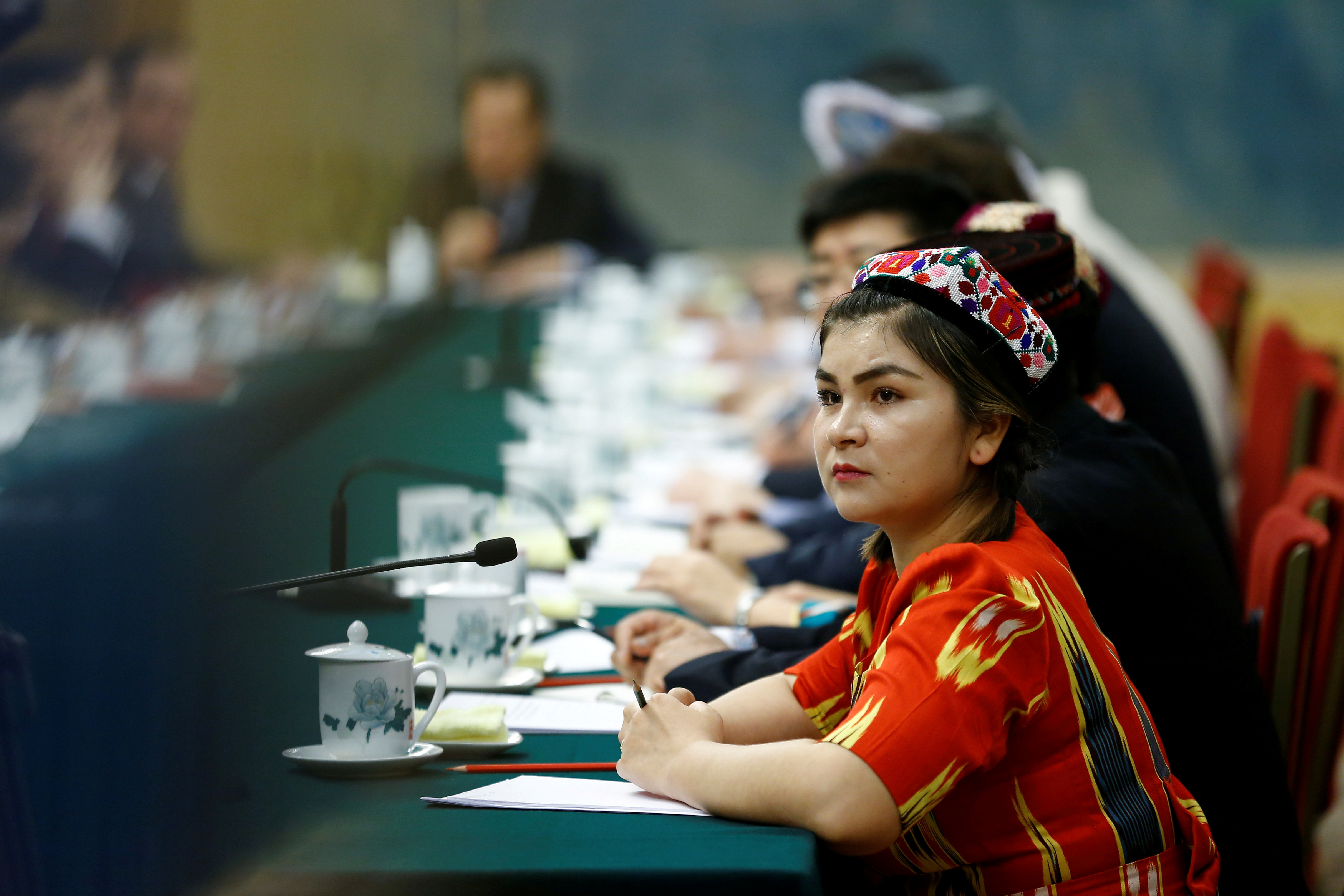 A delegate wearing a traditional costume attends a session of the Xinjiang Uyghur Autonomous Region on the sidelines of the National People's Congress (NPC) at the Great Hall of the People in Beijing, China, March 13, 2018.  REUTERS/Thomas Peter/File Photo