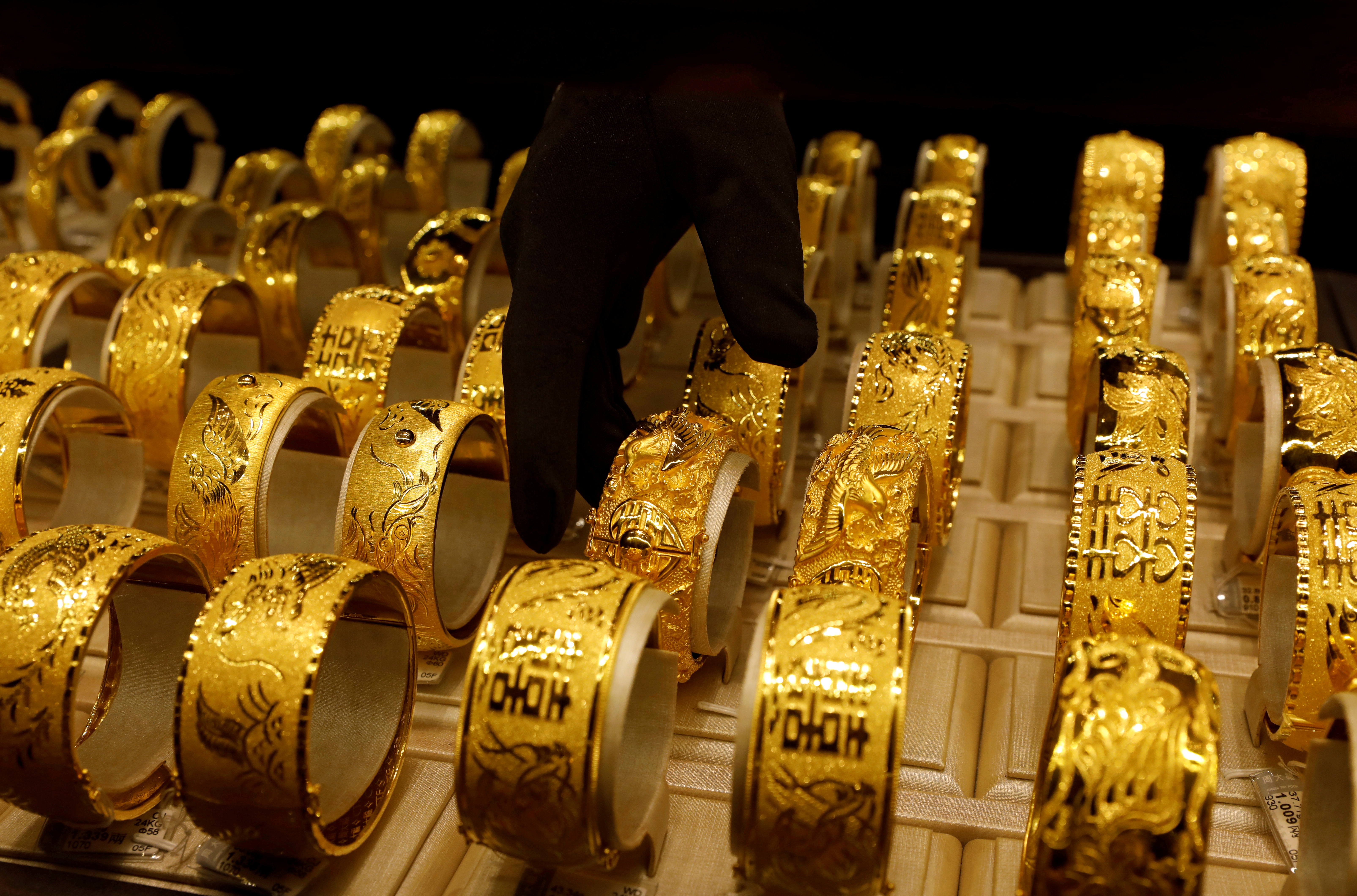 A salesperson arranges 24K gold bracelets for Chinese weddings at Chow Tai Fook Jewellery store in Hong Kong, China December 14, 2017. REUTERS/Tyrone Siu/File Photo