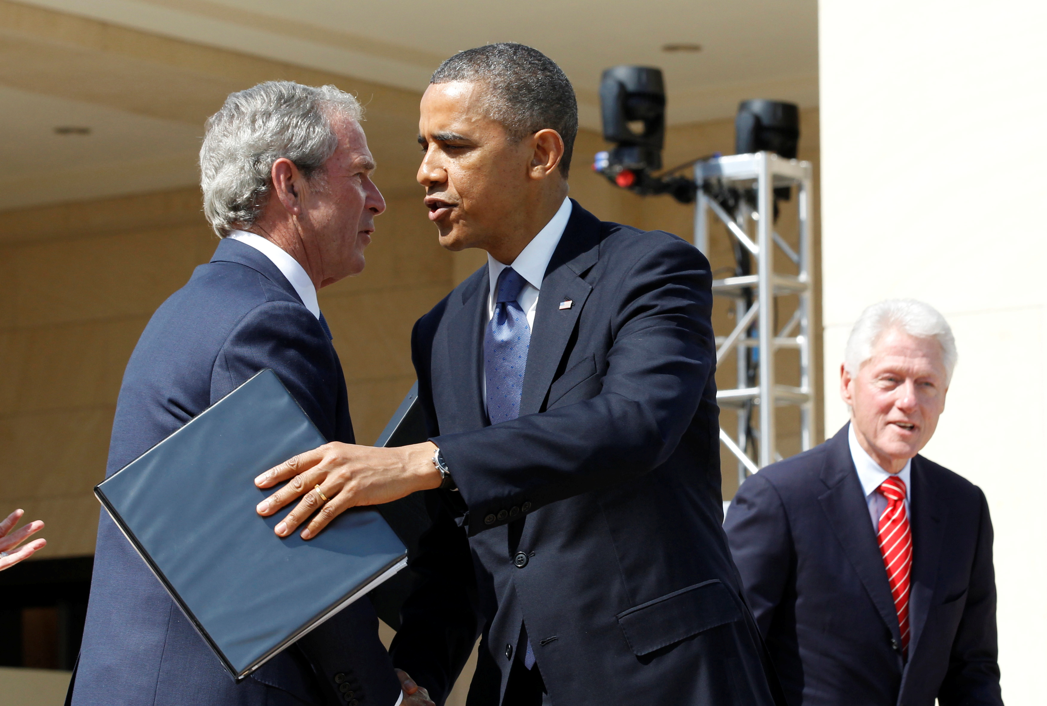 U.S. President Barack Obama embraces former President George W. Bush following remarks at the dedication ceremony of the George W. Bush Presidential Center in Dallas, April 25, 2013. Former president Bill Clinton is pictured at right. REUTERS/Jason Reed/File Photo