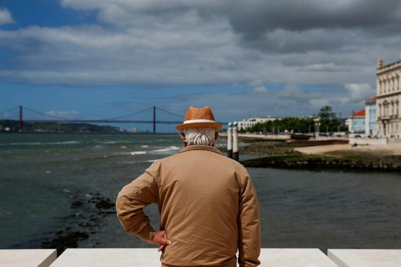A man looks at Tagus river from Praca do Comercio amid the coronavirus disease (COVID-19) pandemic in Lisbon, Portugal, May 11, 2021. REUTERS/Pedro Nunes/File Photo