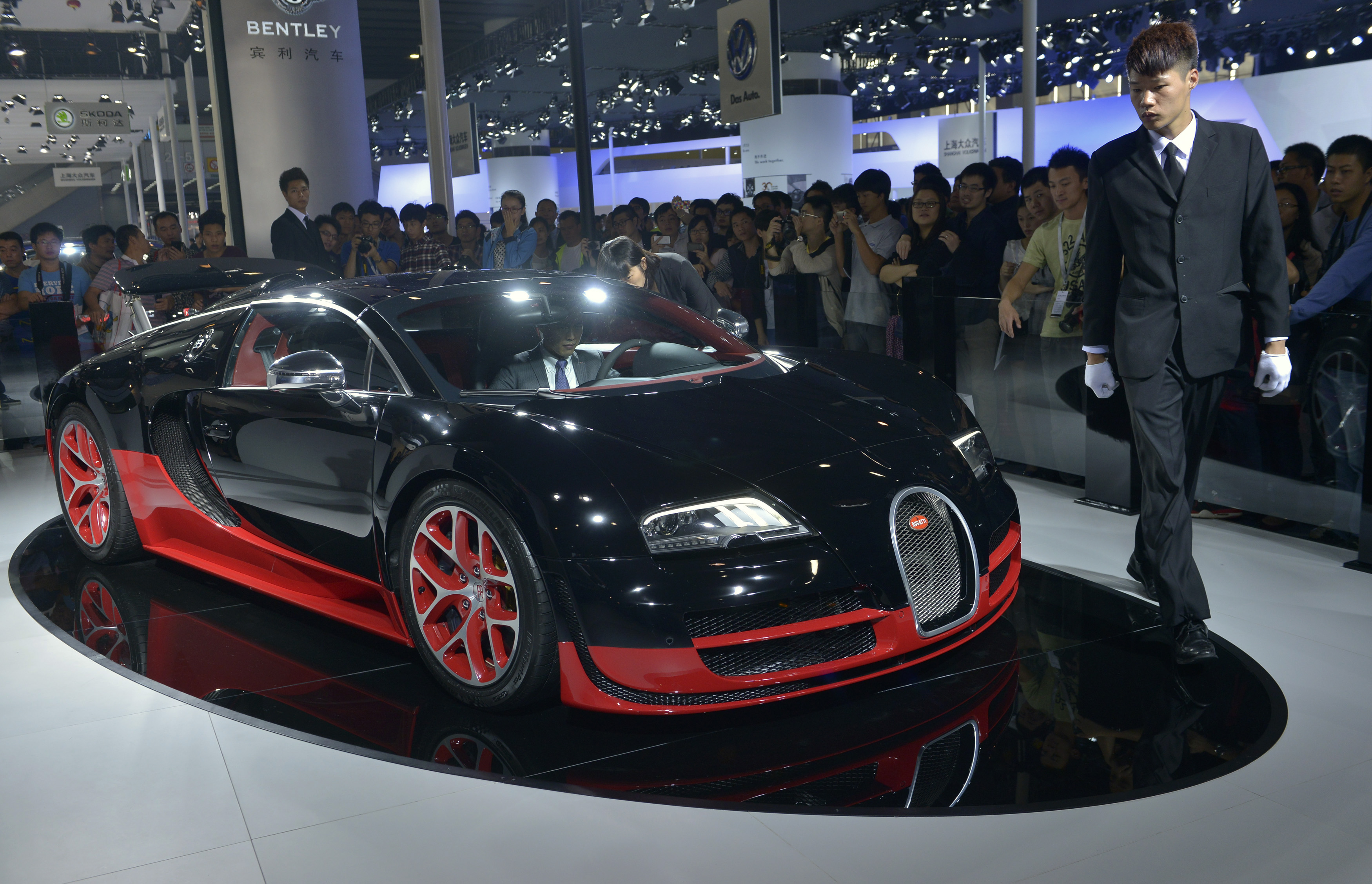 A site organizer walks by a Bugatti Veyron at the Guangzhou International Automobile Exhibition in Guangzhou, Guangdong province, November 22, 2013. Luxury car dealers are resorting to offering customers massages, mini-golf and other gimmicks, hoping this will give them an edge in a ferociously competitive Chinese market where brand loyalty is less common than in the West. REUTERS/Stringer