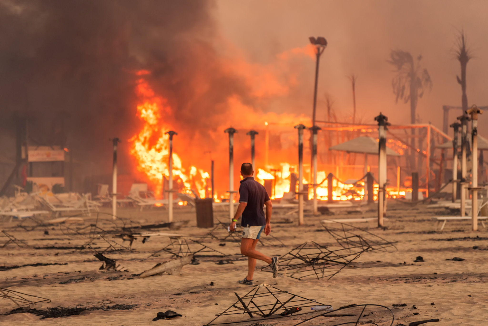A man walks in front of a fire at Le Capannine beach in Catania, Sicily, Italy, July 30, 2021, in this photo obtained from social media on July 31, 2021.  Roberto Viglianisi/via REUTERS