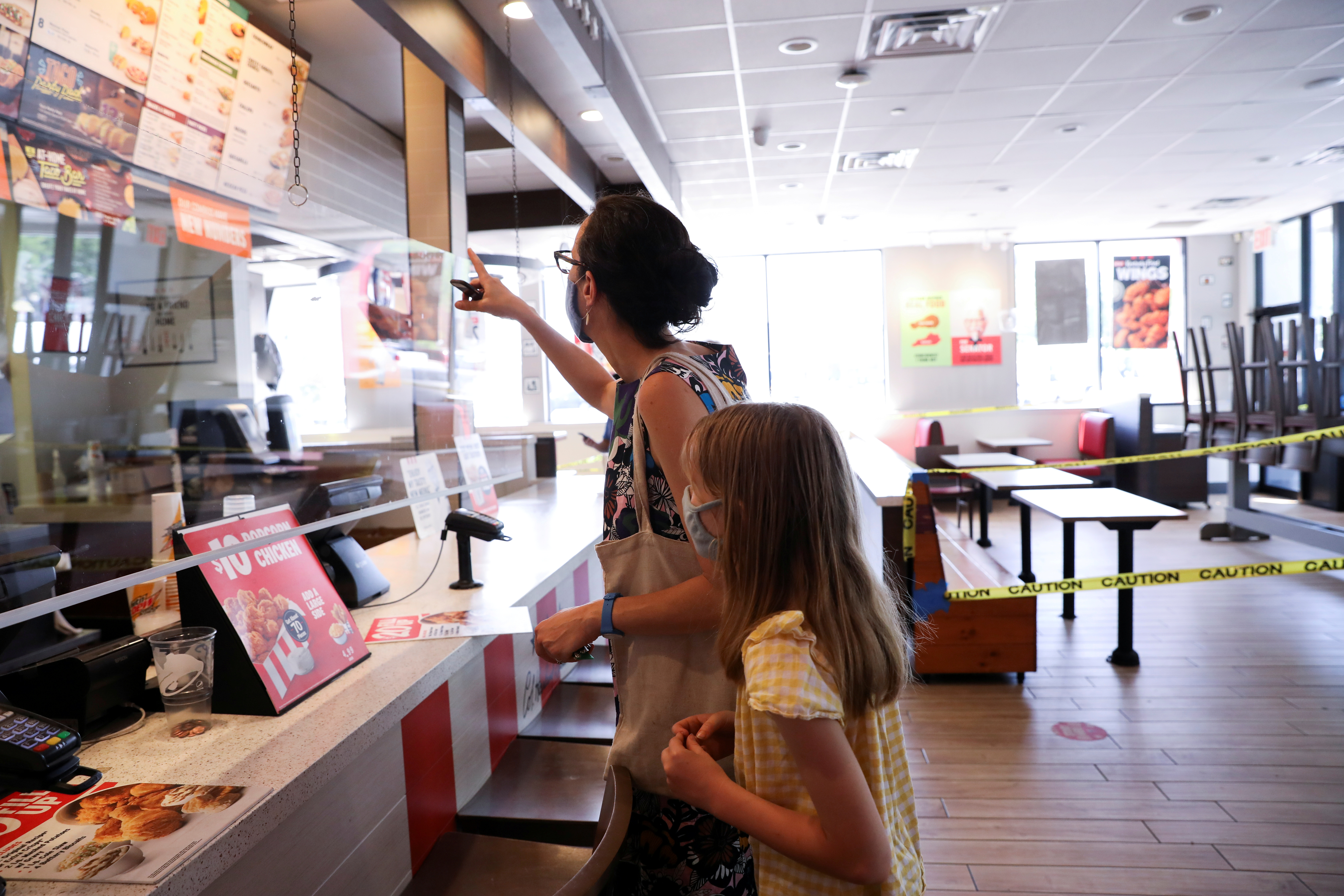 Naomi and Lydia Hassebroek order food from Taco Bell during the outbreak of the coronavirus disease (COVID-19) in Brooklyn, New York, U.S., June 23, 2020. REUTERS/Caitlin Ochs/File Photo