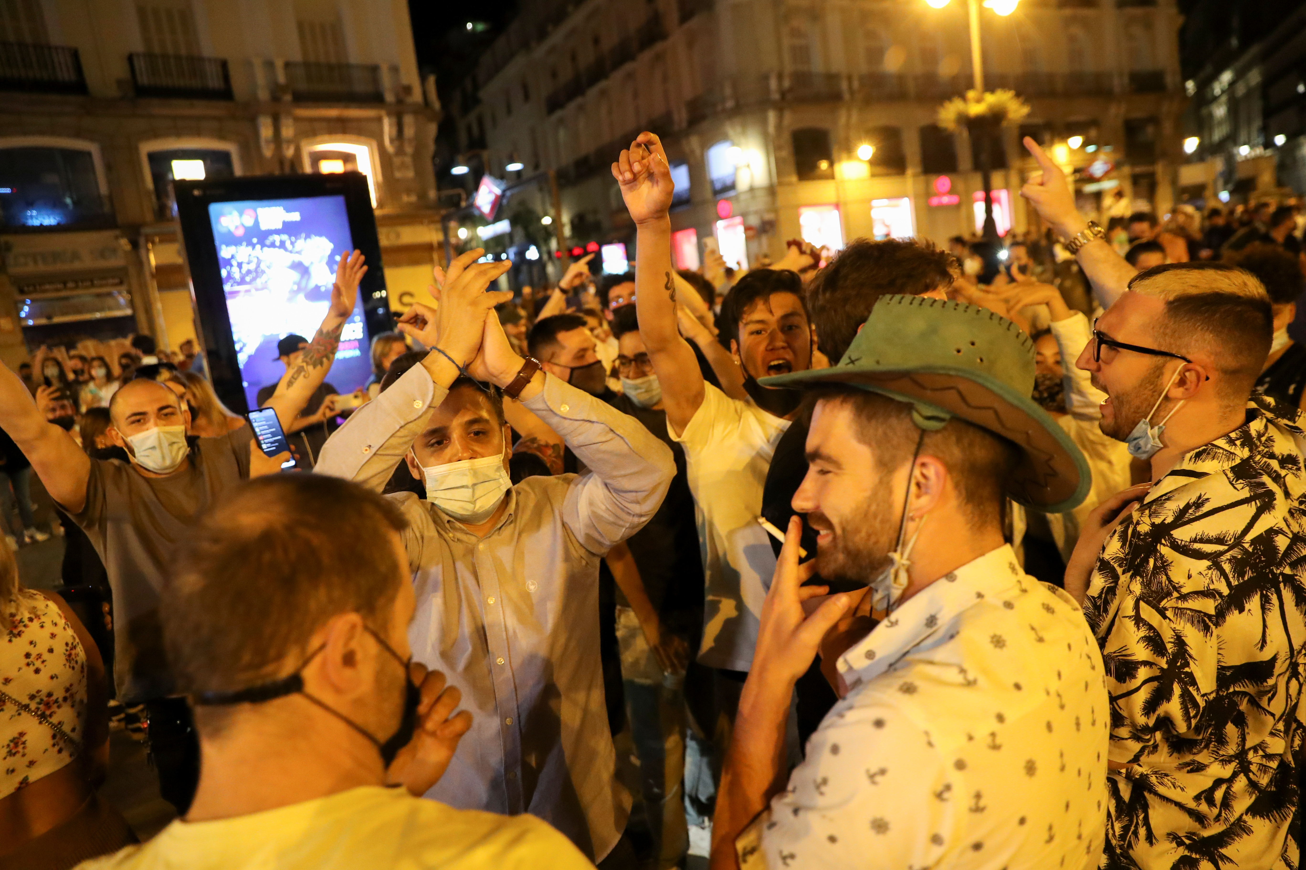 People celebrate as the state of emergency decreed by the Spanish Government to prevent the spread of the coronavirus disease (COVID-19) gets lifted at Puerta del Sol square in Madrid, Spain, May 9, 2021. REUTERS/Susana Vera