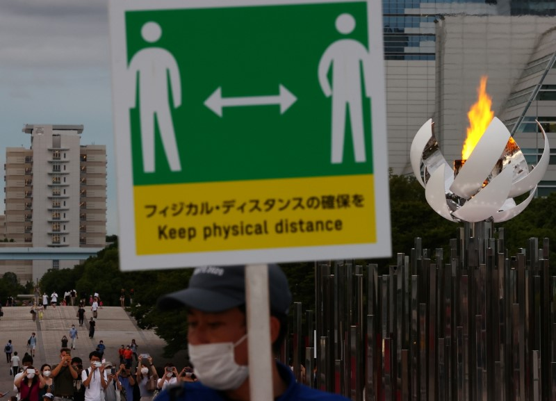 A staff wearing a protective mask, amid the coronavirus disease (COVID-19) outbreak, holds a social distance sign in front of the second Olympic flame cauldron of Tokyo 2020 Olympic Games in Tokyo, Japan, August 7, 2021.  REUTERS/Kim Kyung-Hoon