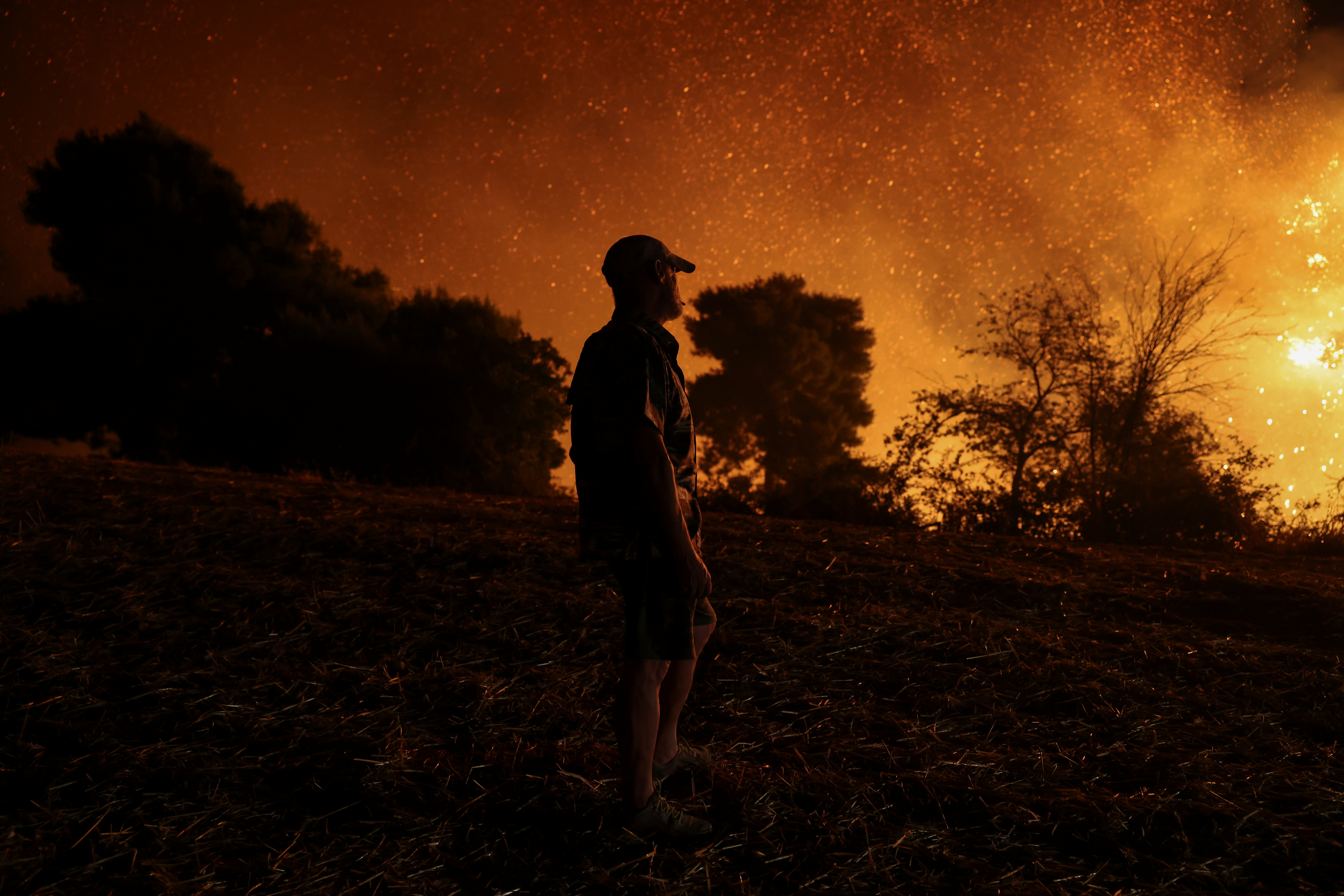 A man is silhouetted as he watches a wildfire burning in the village of Lasdikas near ancient Olympia, Greece, August 5, 2021. REUTERS/Giorgos Moutafis