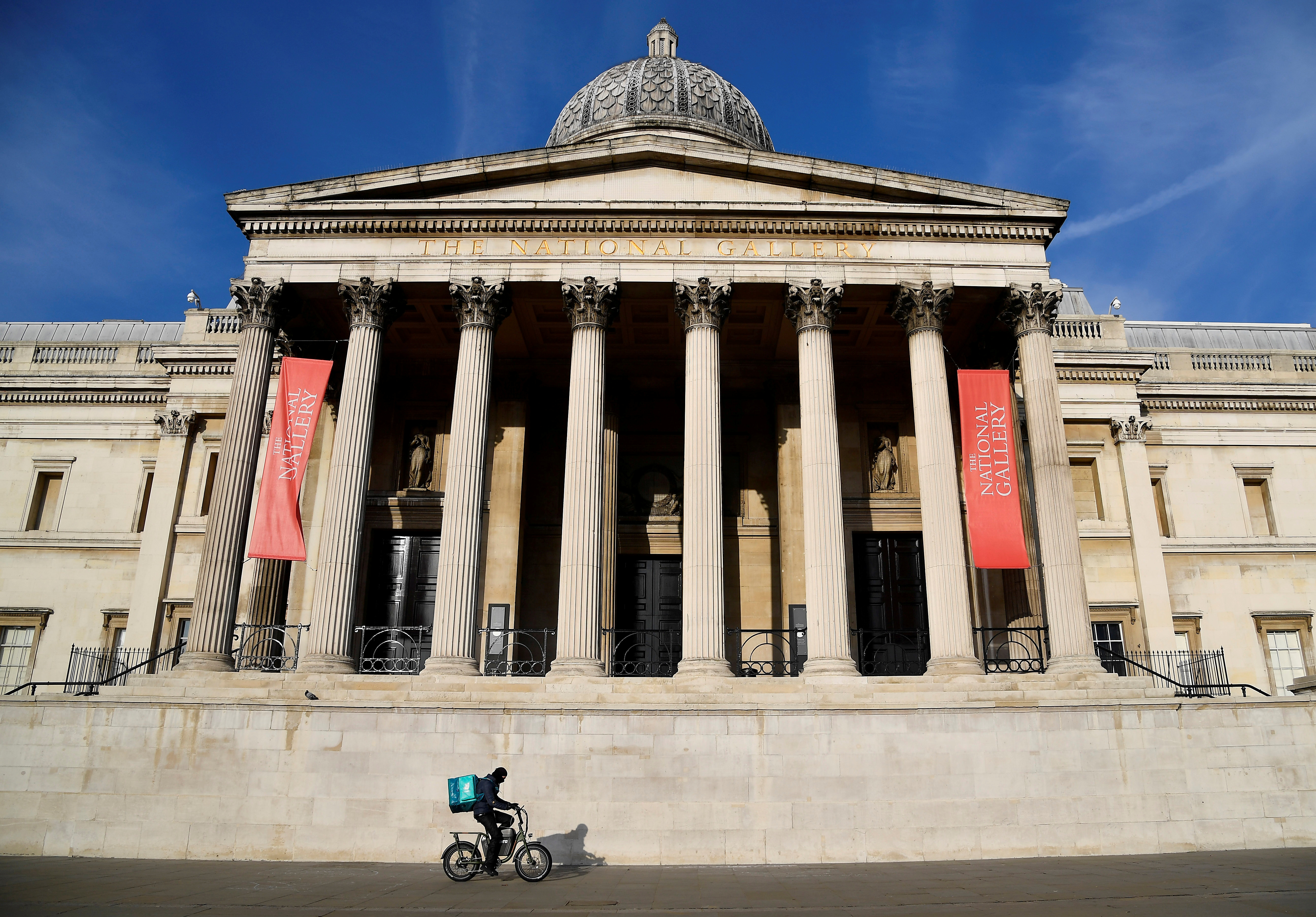 Deliveroo rider cycles past the closed National Gallery amidst the COVID-19 pandemic lockdown in London, Britain, January 7, 2021. REUTERS/Toby Melville/File Photo