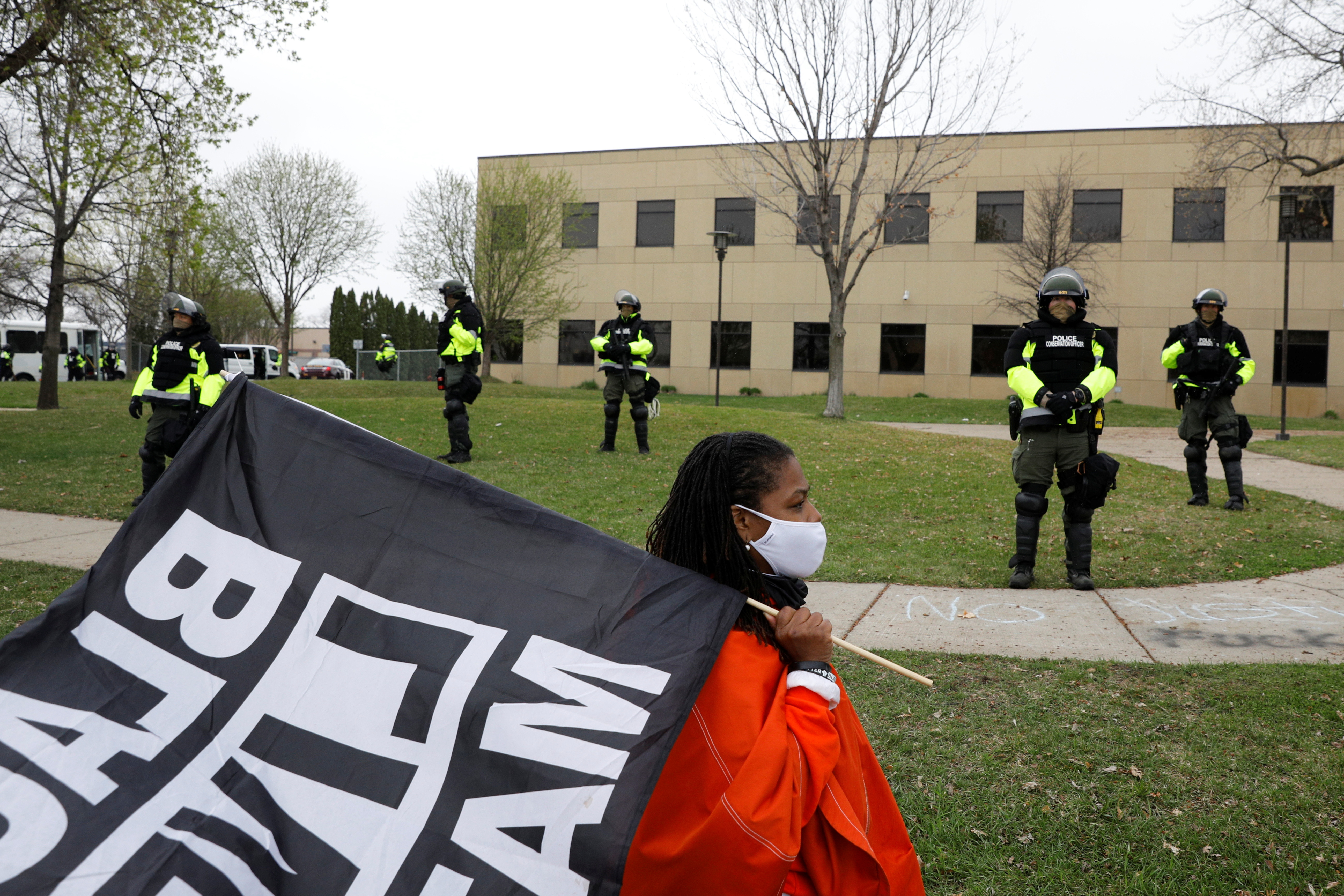 An activist paces in front of officers at the Brooklyn Center Police Department after an officer-involved killing of Daunte Wright, 20, following a traffic stop in Brooklyn Center, Minnesota, U.S., April 12, 2021. REUTERS/Nicholas Pfosi