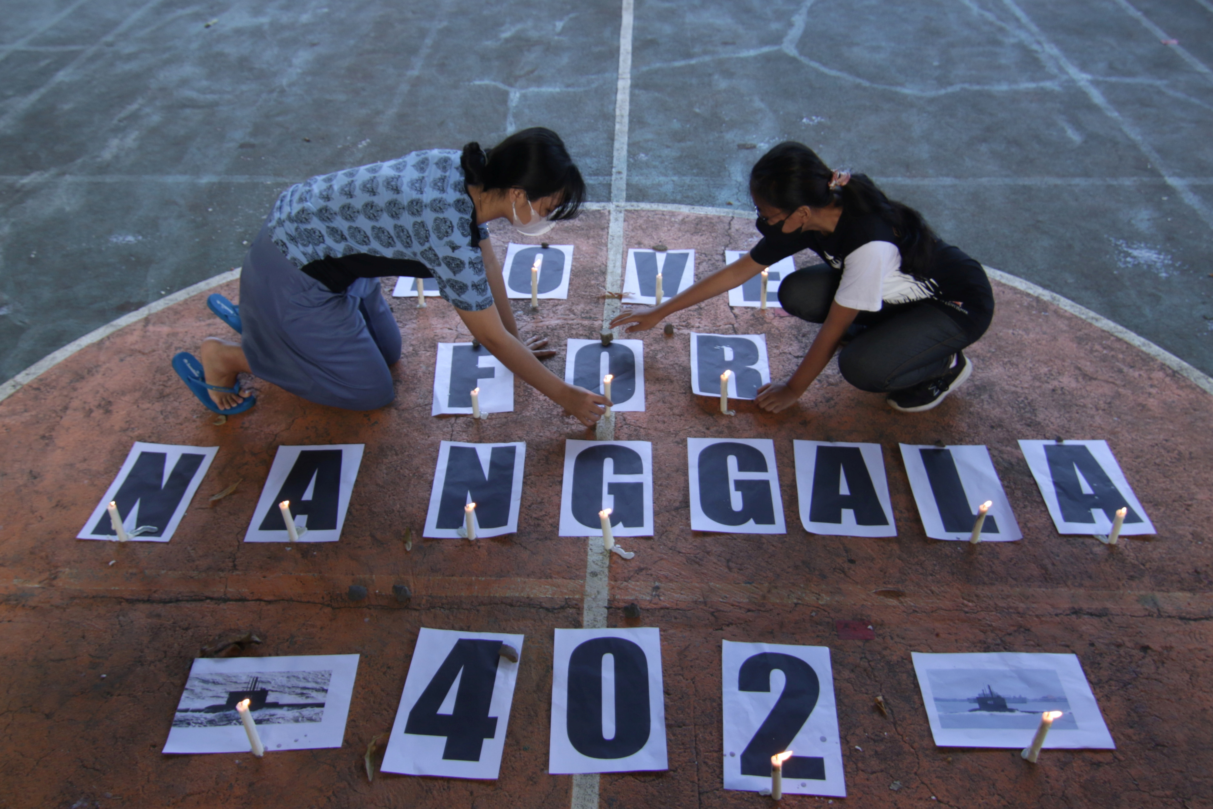 Students arrange the candles during a vigil for crew members who onboard the submarine KRI-402, sunk at the north Bali sea during a drill, in Banyuwangi, East Java province, Indonesia, April 27, 2021 in this photo taken by Antara Foto/Budi Candra Setya/via REUTERS