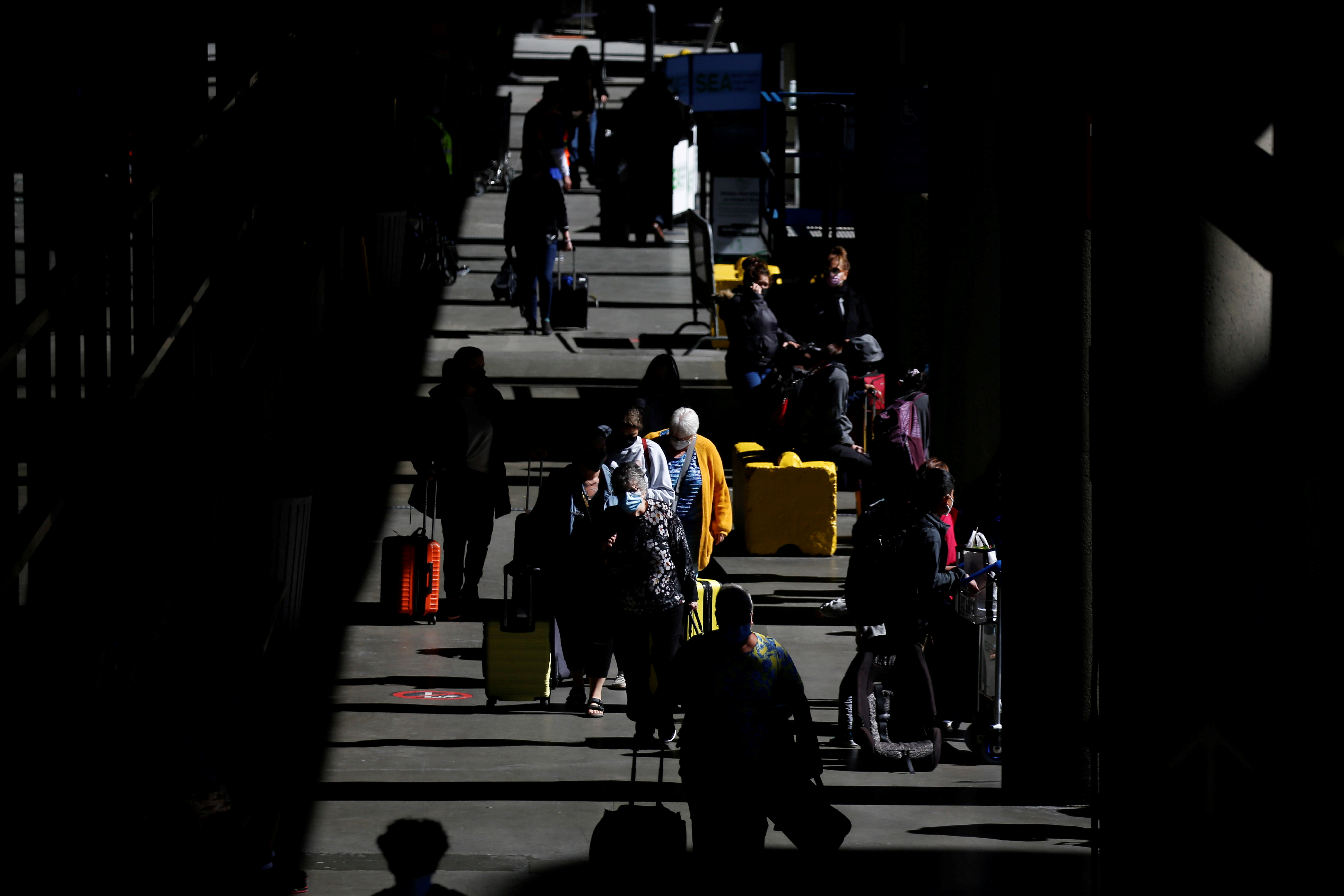 Travelers walk through a pick-up area in the arrivals section at Seattle-Tacoma International Airport in SeaTac, Washington, U.S. April 12, 2021.  REUTERS/Lindsey Wasson