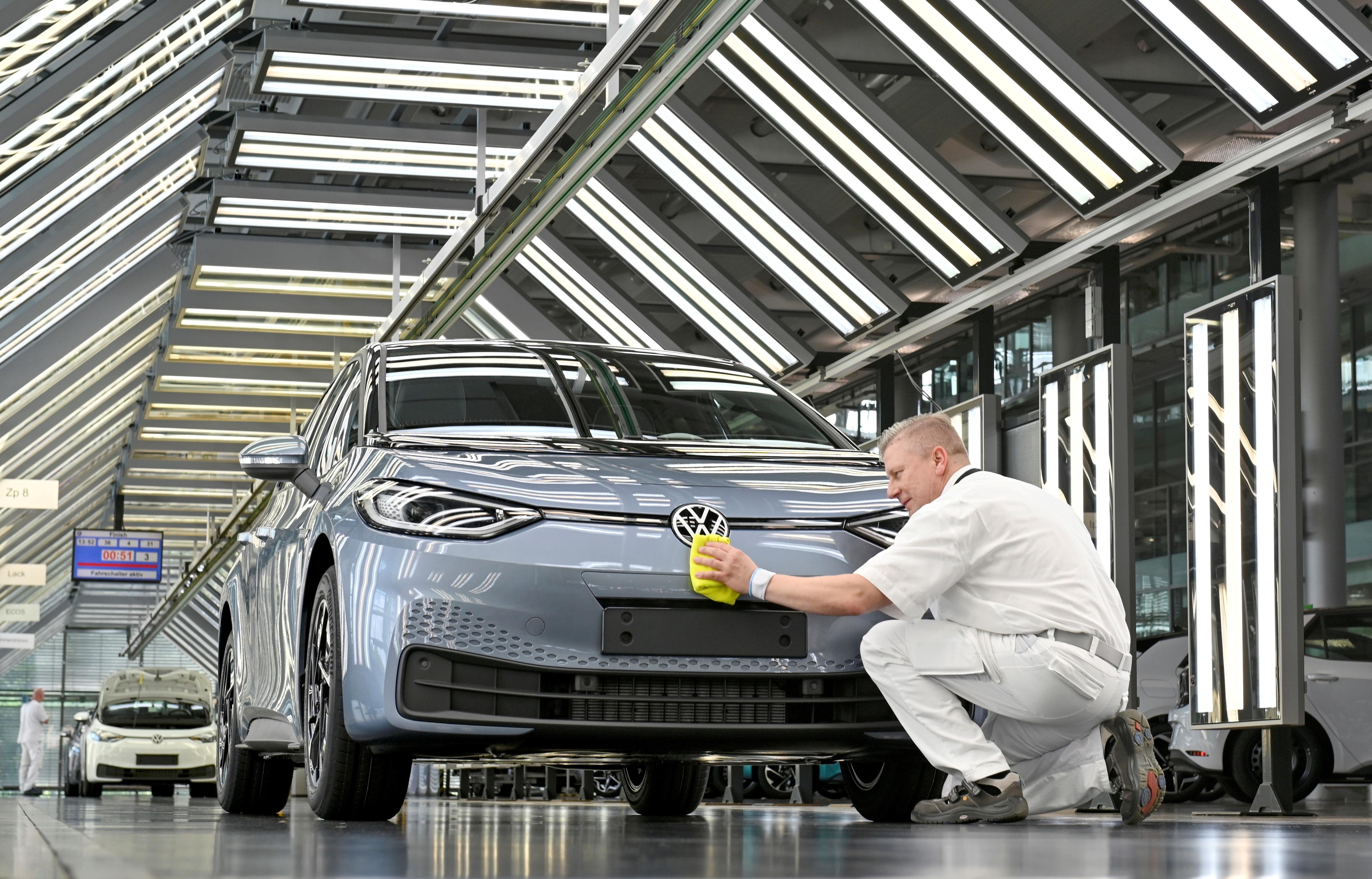Technicians work in the final inspection line of German carmaker Volkswagen's electric ID. 3 car in Dresden, Germany, June 8, 2021. REUTERS/Matthias Rietschel/File Photo