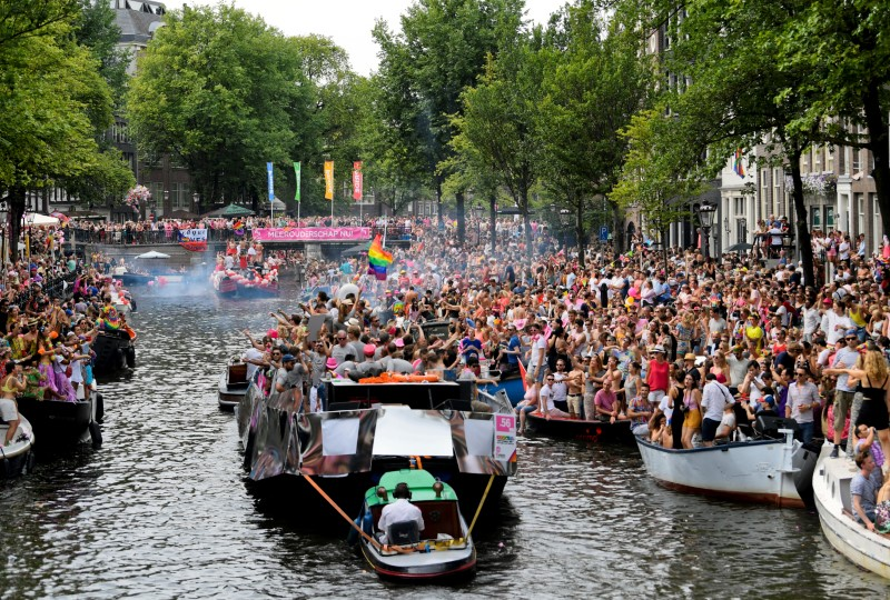 Boats filled with participants cruise the World Heritage canals during the annual gay pride parade in Amsterdam, Netherlands August 4, 2018. REUTERS/Piroschka van de Wouw