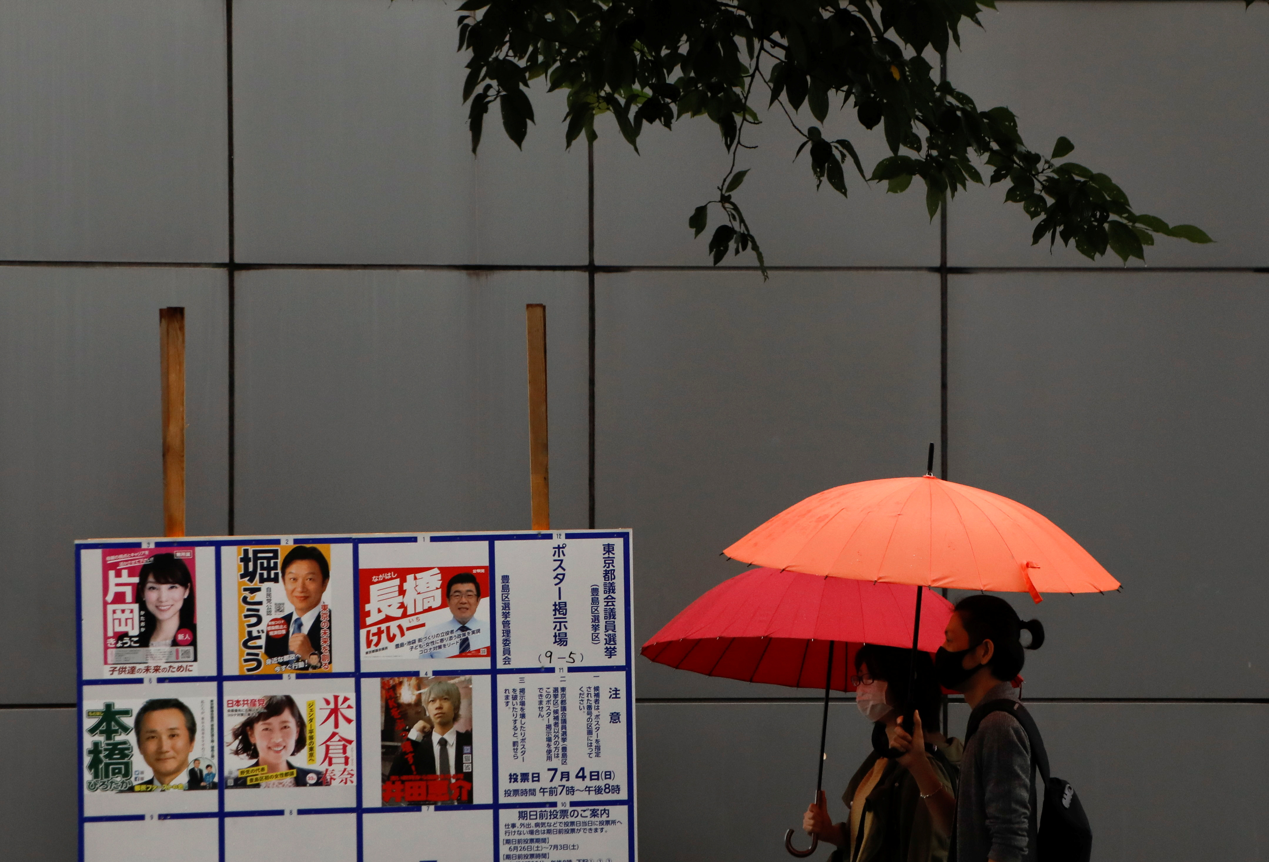 Voters wearing protective face masks walk next to a board displaying posters of candidates for the Tokyo Metropolitan Assembly election near a polling station, amid the coronavirus disease (COVID-19) outbreak, in Tokyo, Japan July 4, 2021.  REUTERS/Issei Kato