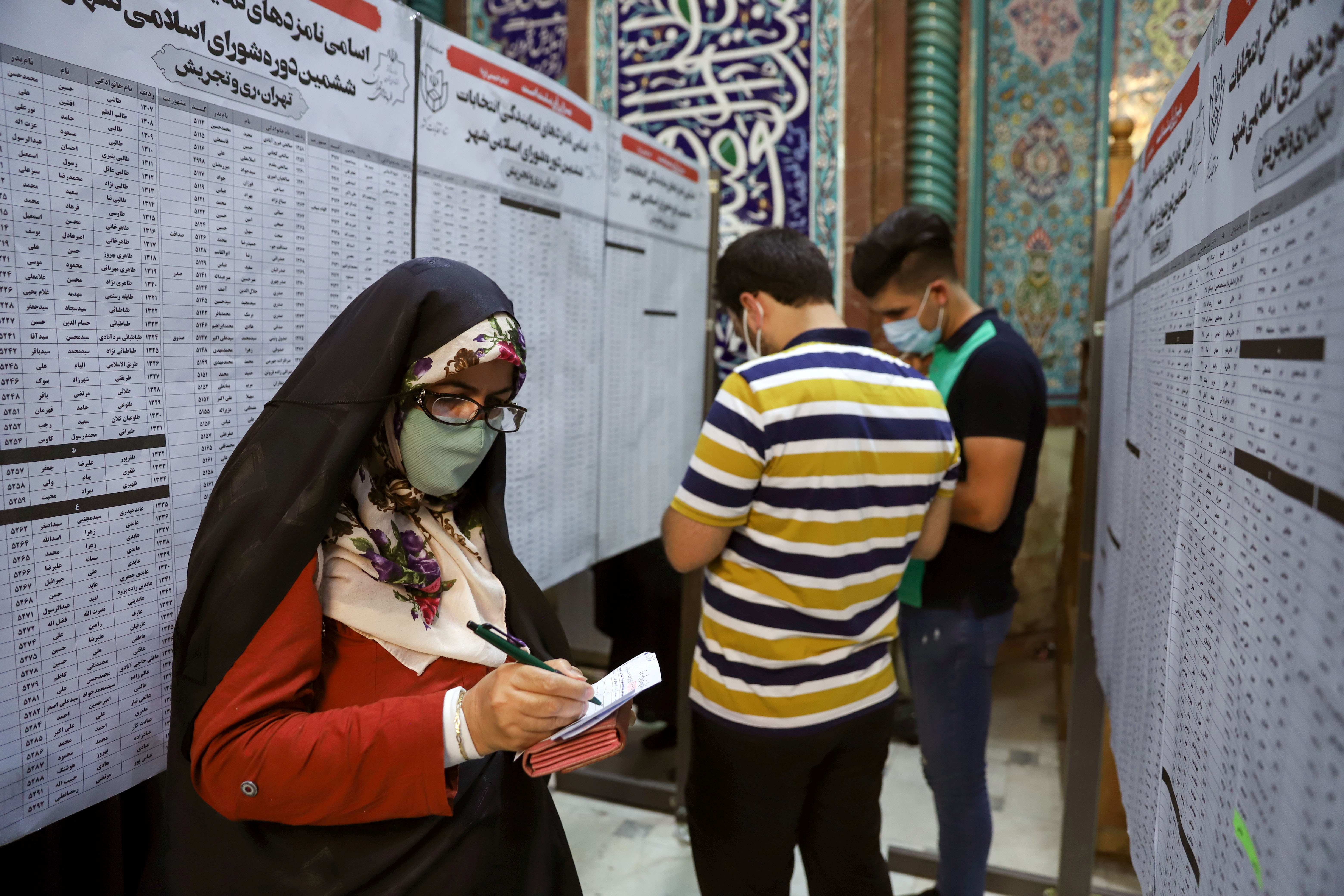 Iranian people check the names of candidates during presidential elections at a polling station in Tehran, Iran June 18, 2021. Majid Asgaripour/WANA (West Asia News Agency) via REUTERS
