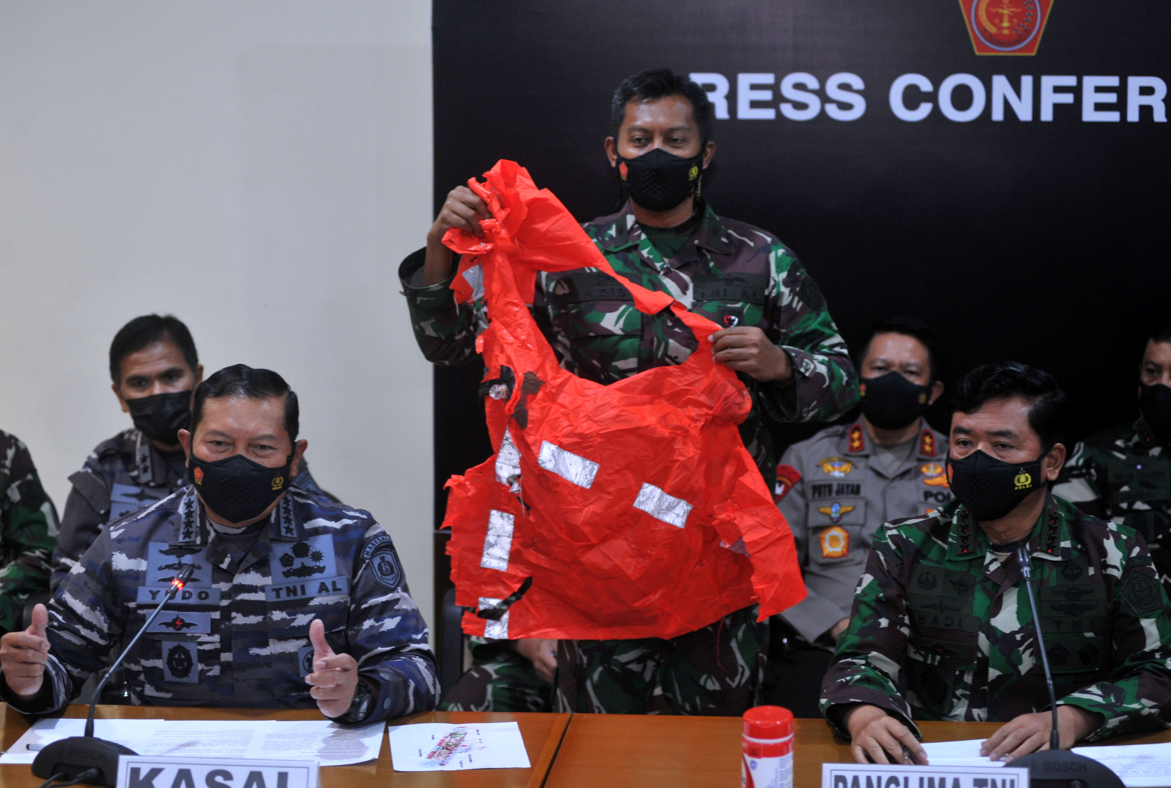 A military personnel holds an escape suit believed to be from the sunken Indonesian Navy KRI Nanggala-402 submarine during a media conference at I Gusti Ngurah Rai Airport in Bali, Indonesia April 25, 2021, in this photo taken by Antara Foto/Fikri Yusuf/via REUTERS