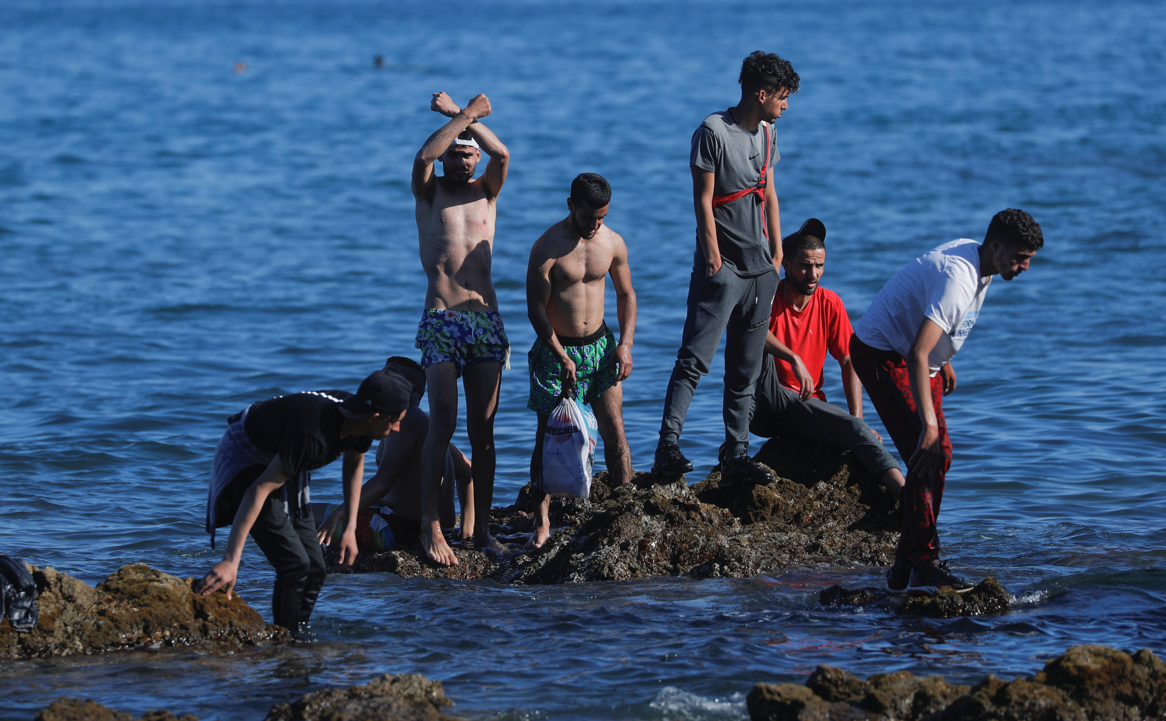 Moroccan citizens stand on the rocks at El Tarajal beach, near the fence between the Spanish-Moroccan border, after thousands of migrants swam across this border during last days, in Ceuta, Spain, May 18, 2021. REUTERS/Jon Nazca
