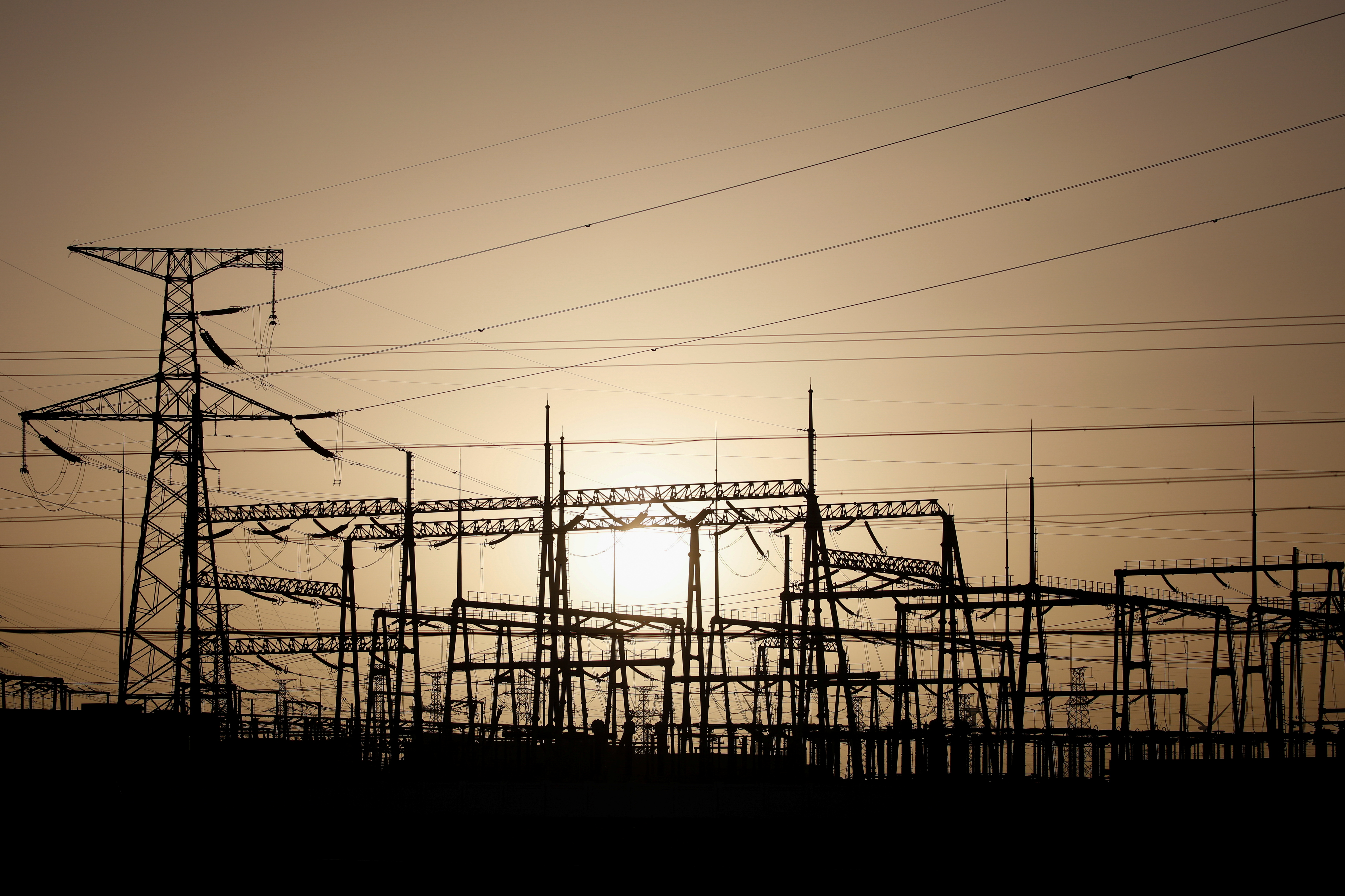Electricity pylons and power lines are pictured at a power station near Yumen, Gansu province, China September 25, 2020. REUTERS/Carlos Garcia Rawlins