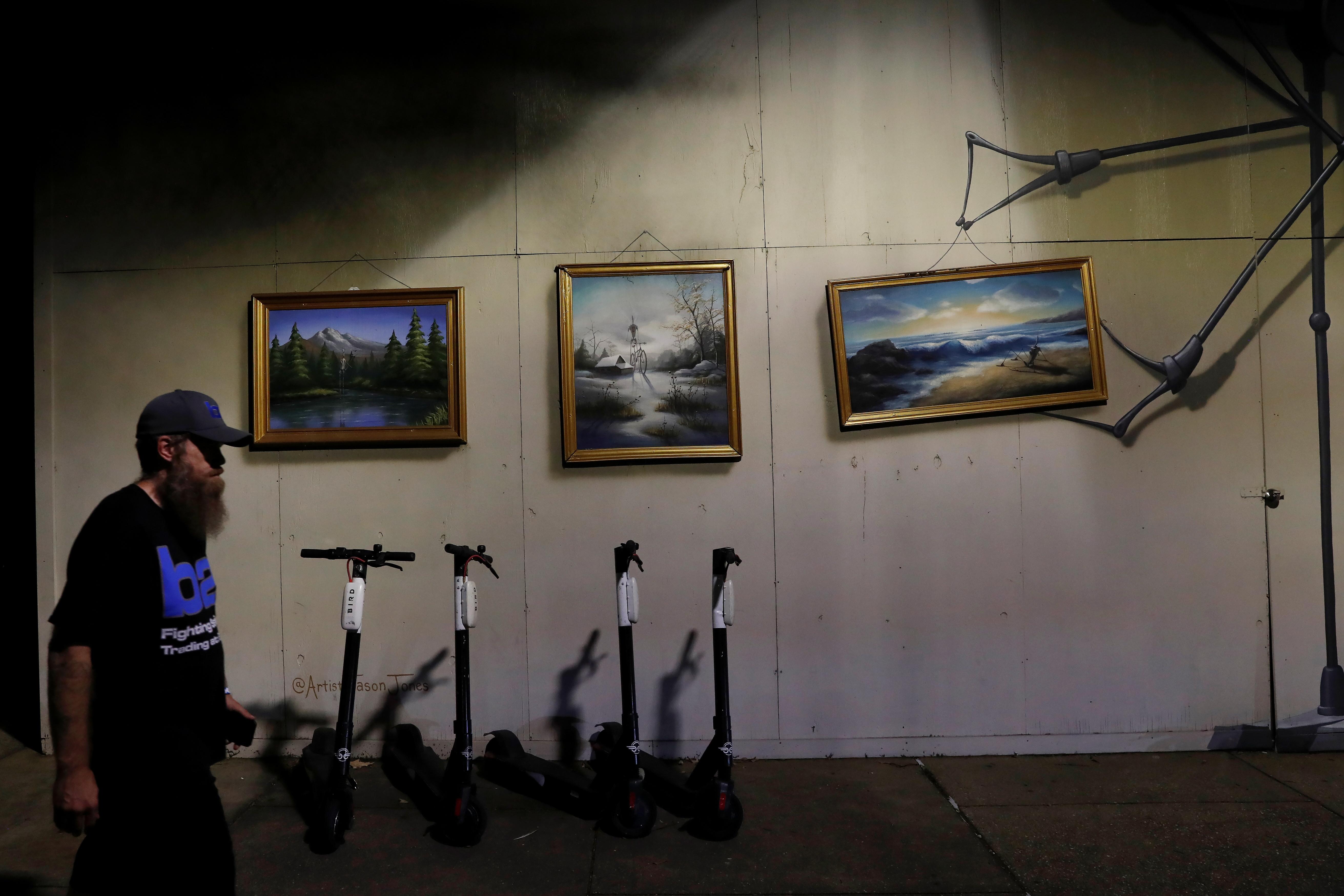 A man walks past hanging paintings, amid the coronavirus disease (COVID-19) pandemic, along Main Street in Little Rock, Arkansas, U.S., August 13, 2021. REUTERS/Shannon Stapleton