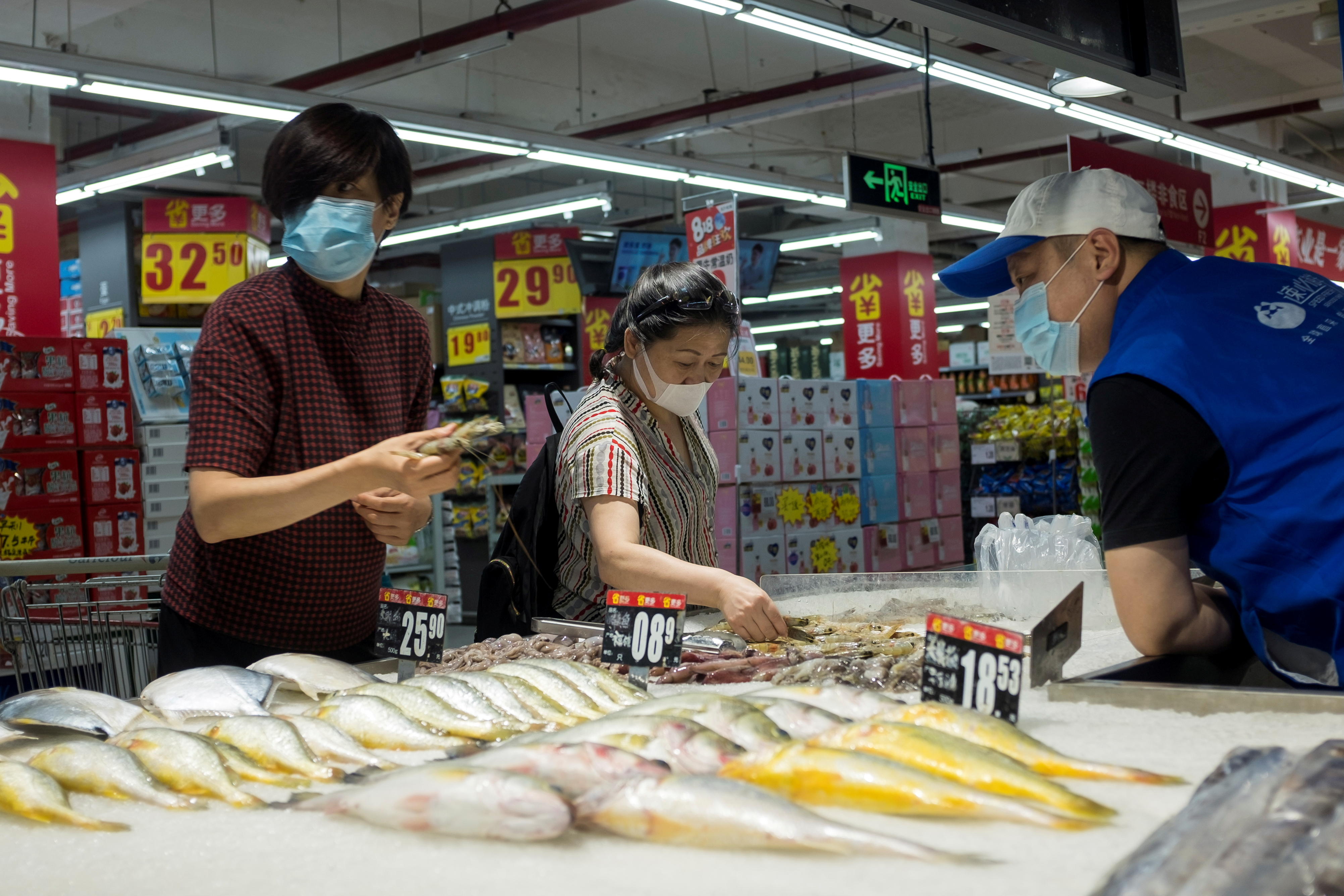 People look at fresh seafood in a supermarket following an outbreak of the coronavirus disease (COVID-19) in Beijing, China, August 13, 2020. REUTERS/Thomas Peter/File Photo