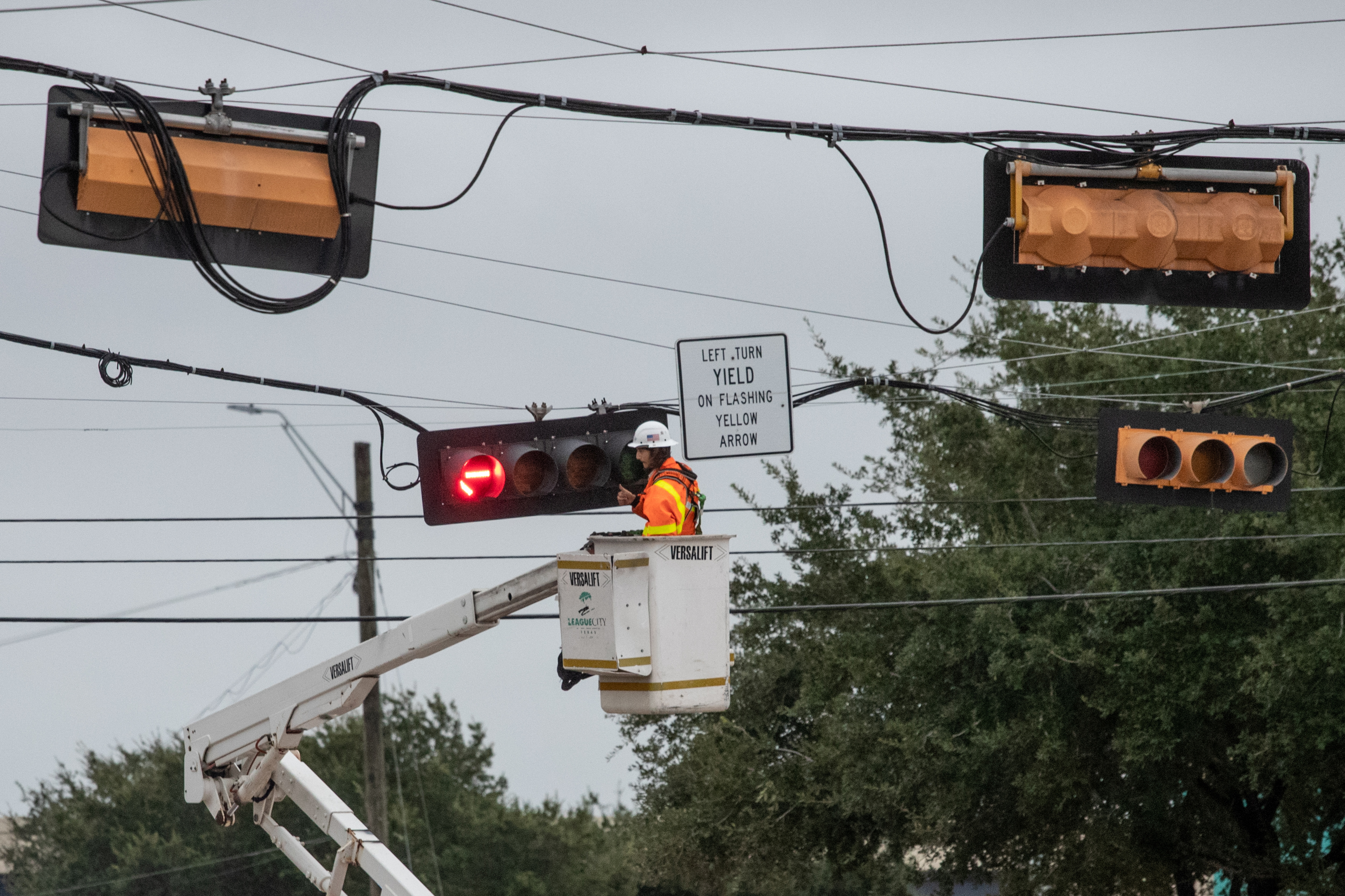 A worker restores power to traffic lights in the aftermath of Hurricane Nicholas in League City, Texas, U.S., September 14, 2021. REUTERS/Adrees Latif