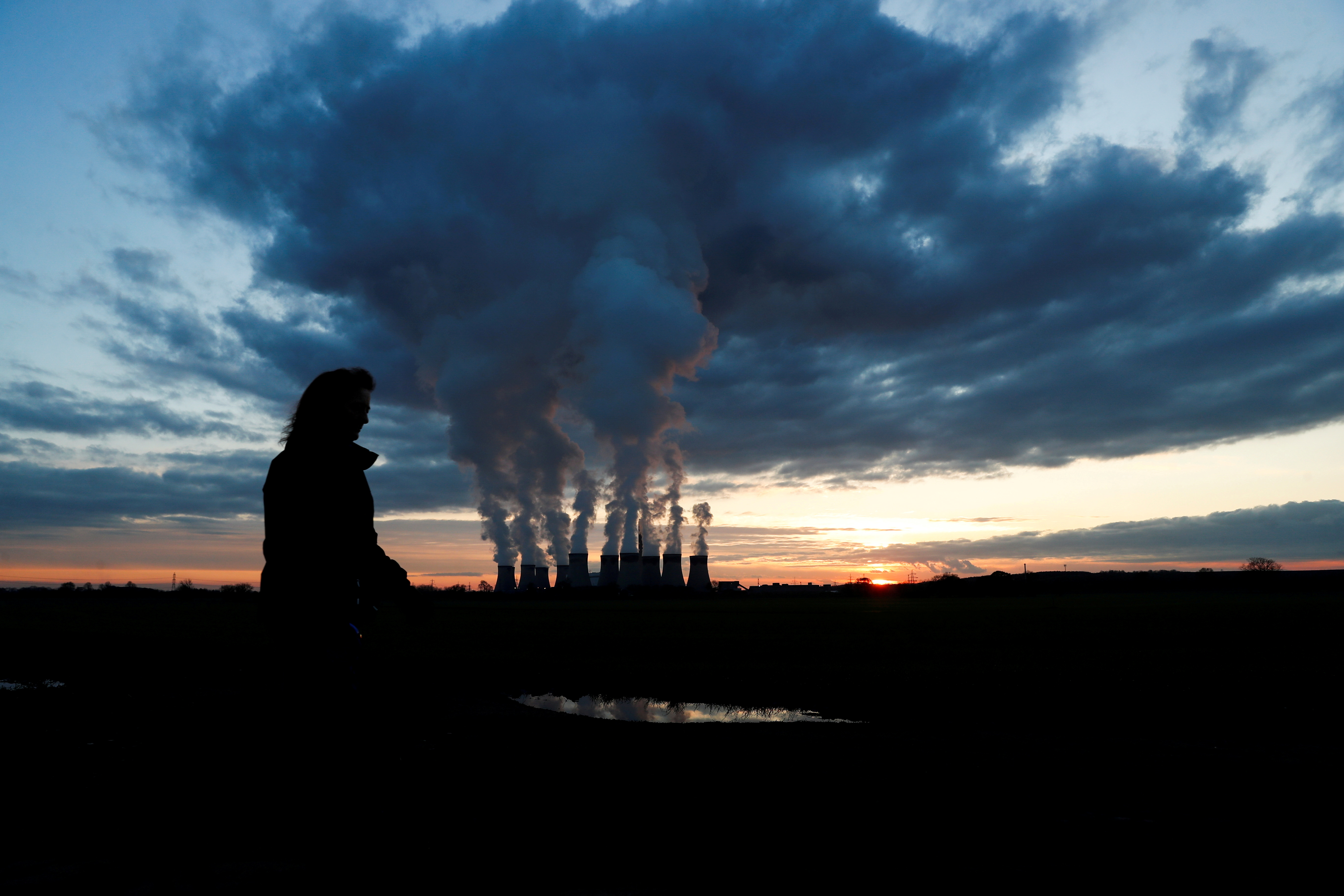 A woman walks a dog past Drax power station during the sunset in Drax, North Yorkshire, Britain, November 27, 2020. REUTERS/Lee Smith/File Photo