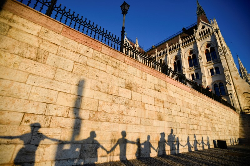 Silhouettes of demonstrators are seen as they march around the Hungarian parliament to protest against Hungarian Prime Minister Viktor Orban and the latest anti-LGBTQ law in Budapest, Hungary, June 14, 2021. REUTERS/Marton Monus/File Photo