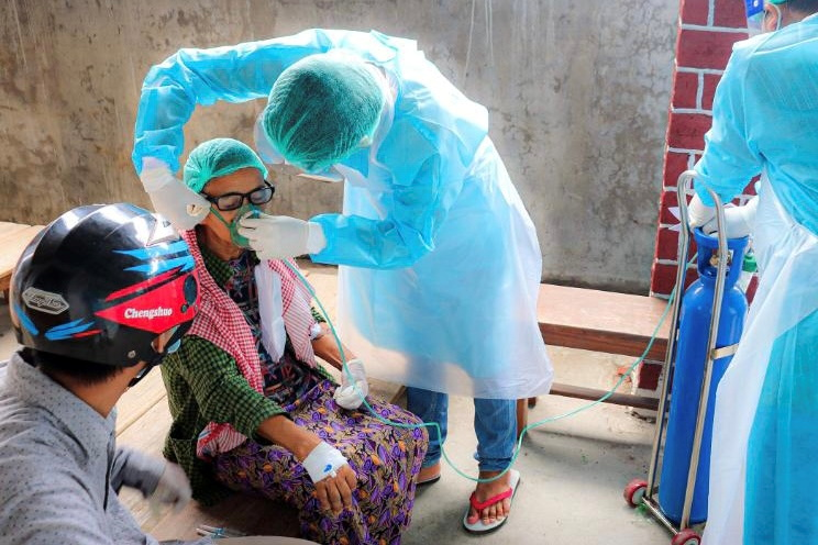 A volunteer adjusts the oxygen mask of a coronavirus (COVID-19) patient in the town of Kale, Sagaing Region, Myanmar, July 5, 2021.   REUTERS/Stringer