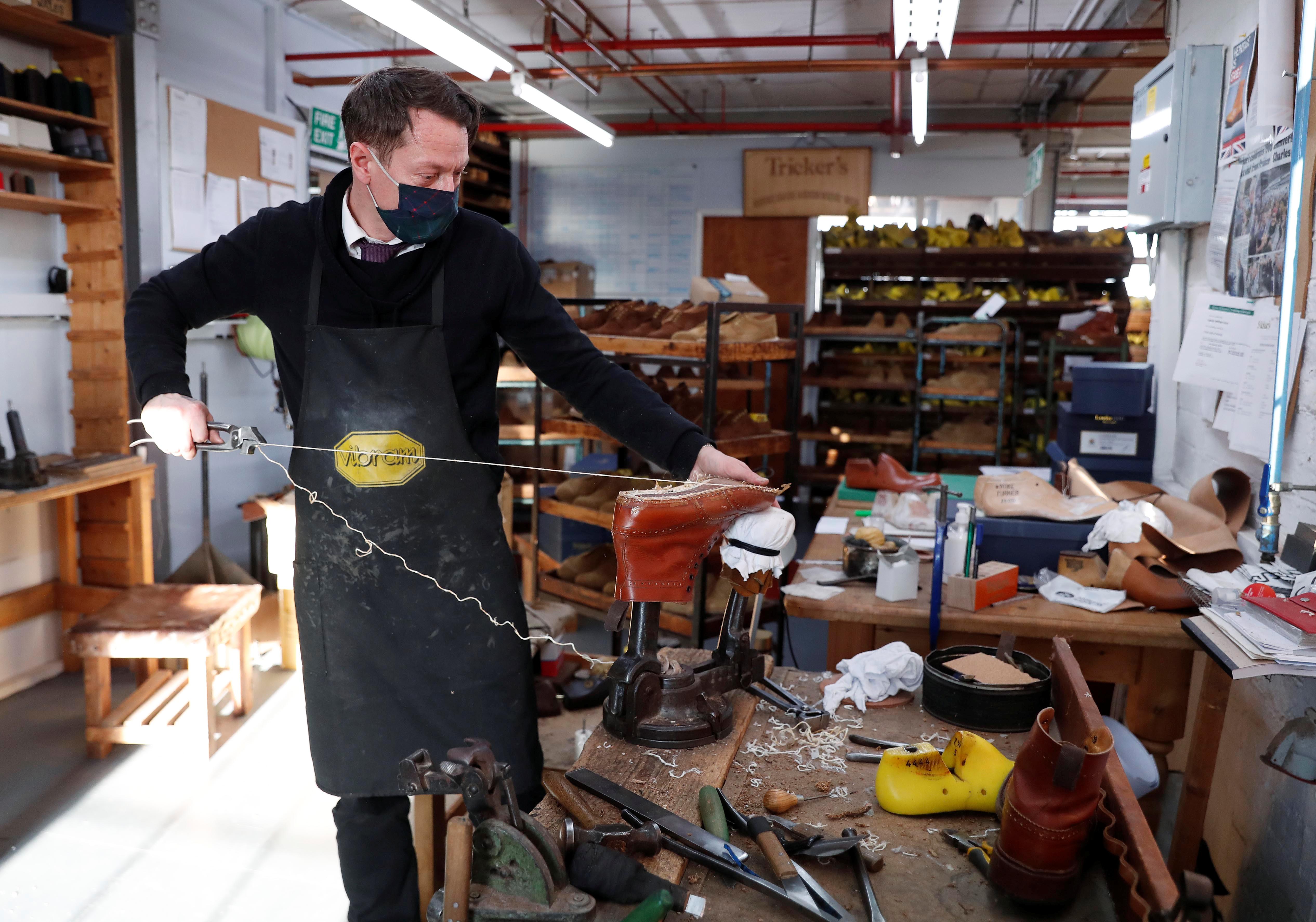 Master Bespoke Shoemaker Scott McKee repairs a shoe at Trickers in Northampton, Britain, January 25, 2021. REUTERS/Matthew Childs