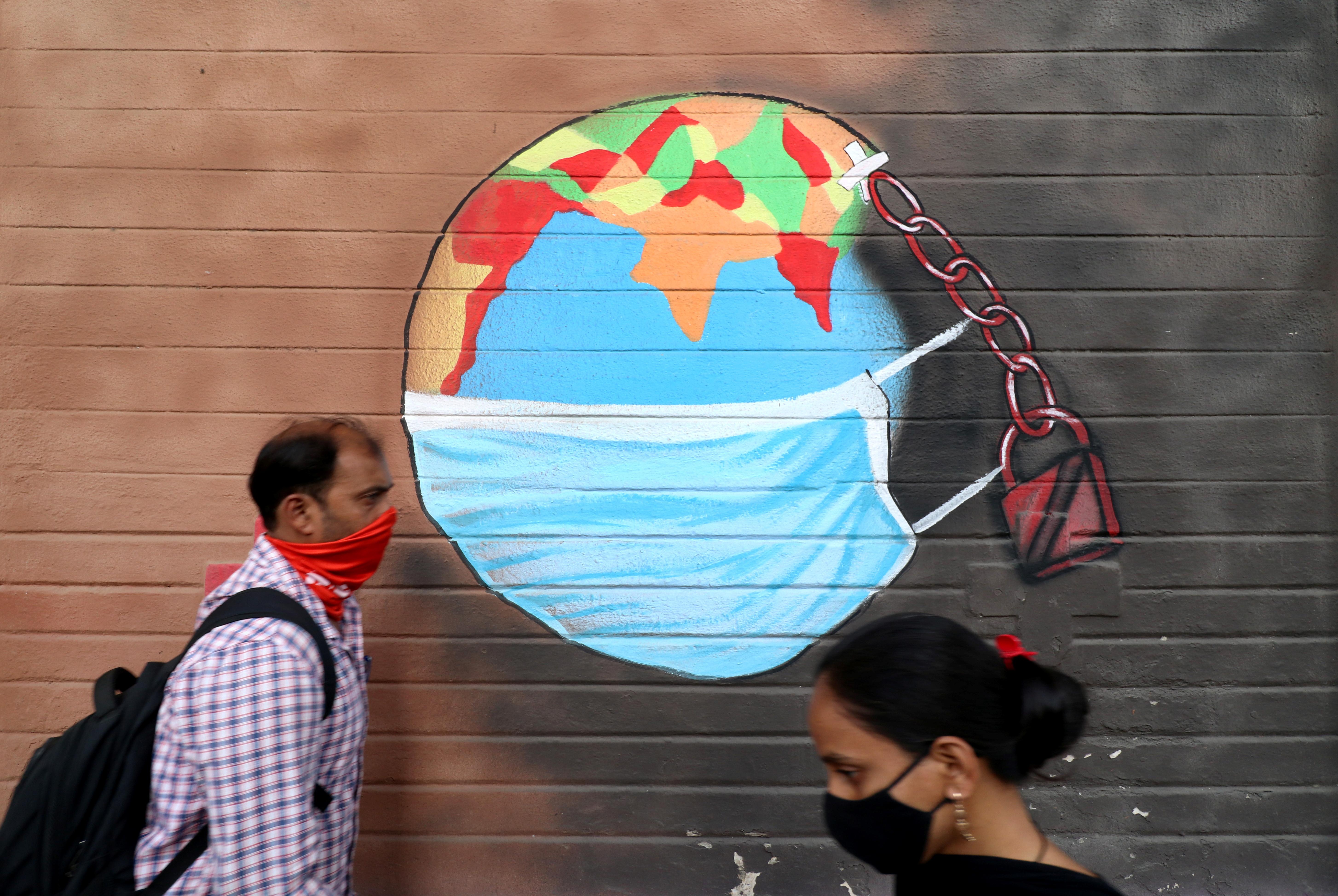 A man and a woman wearing protective face masks walk past a graffiti on a wall, amidst the spread of the coronavirus disease (COVID-19), in Mumbai, India, March 25, 2021. REUTERS/Niharika Kulkarni/File photo