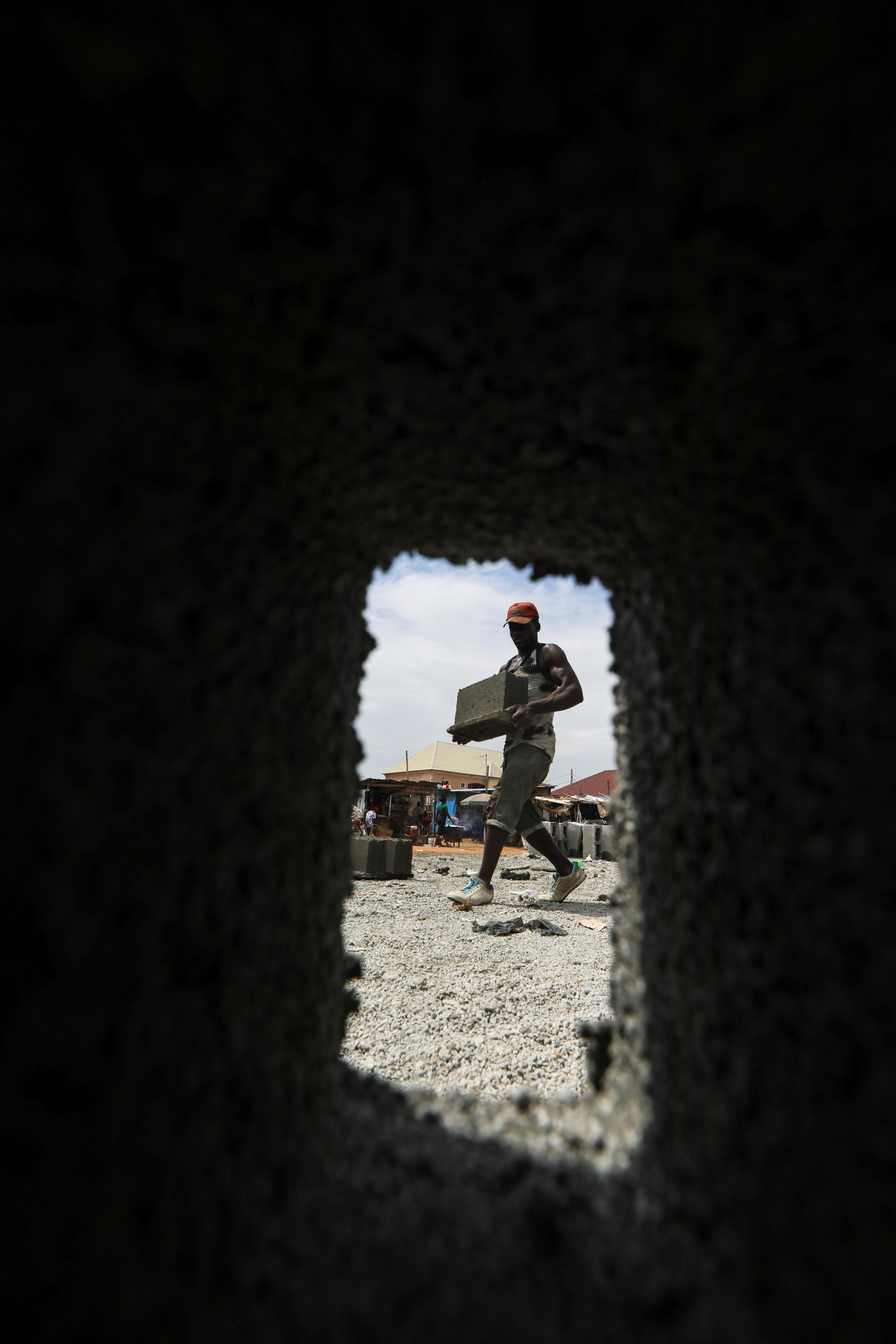 A man carries a moulded block at a block making centre in Abuja, Nigeria May 10, 2021. Picture taken May 10, 2021. REUTERS/Afolabi Sotunde