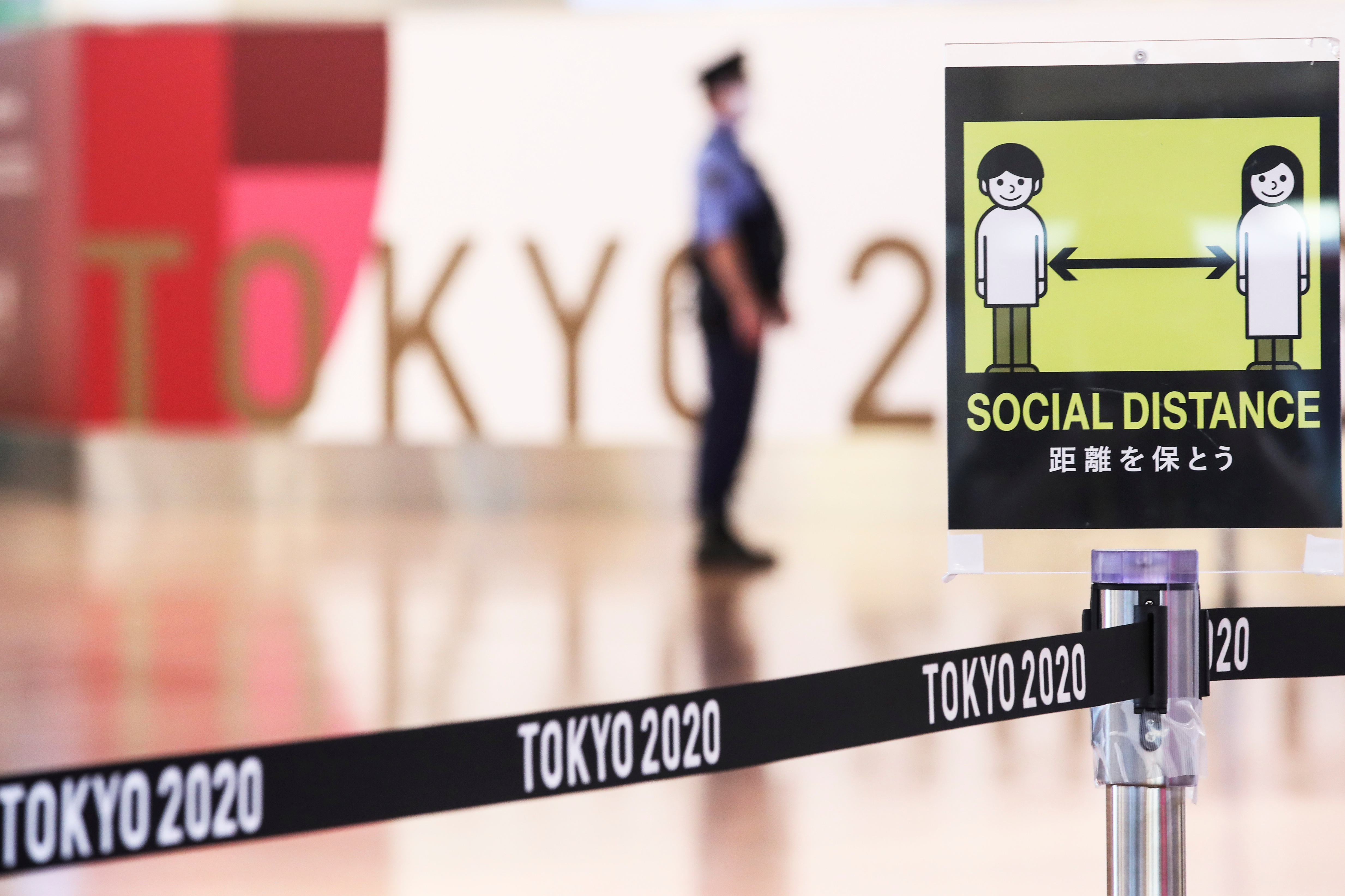 A social distancing sign is seen in front of a police officer before the arrival of International Olympic Committee (IOC) President Thomas Bach at Haneda Airport ahead of Tokyo 2020 Olympic Games, in Tokyo, Japan July 8, 2021. REUTERS/Kim Kyung-Hoon