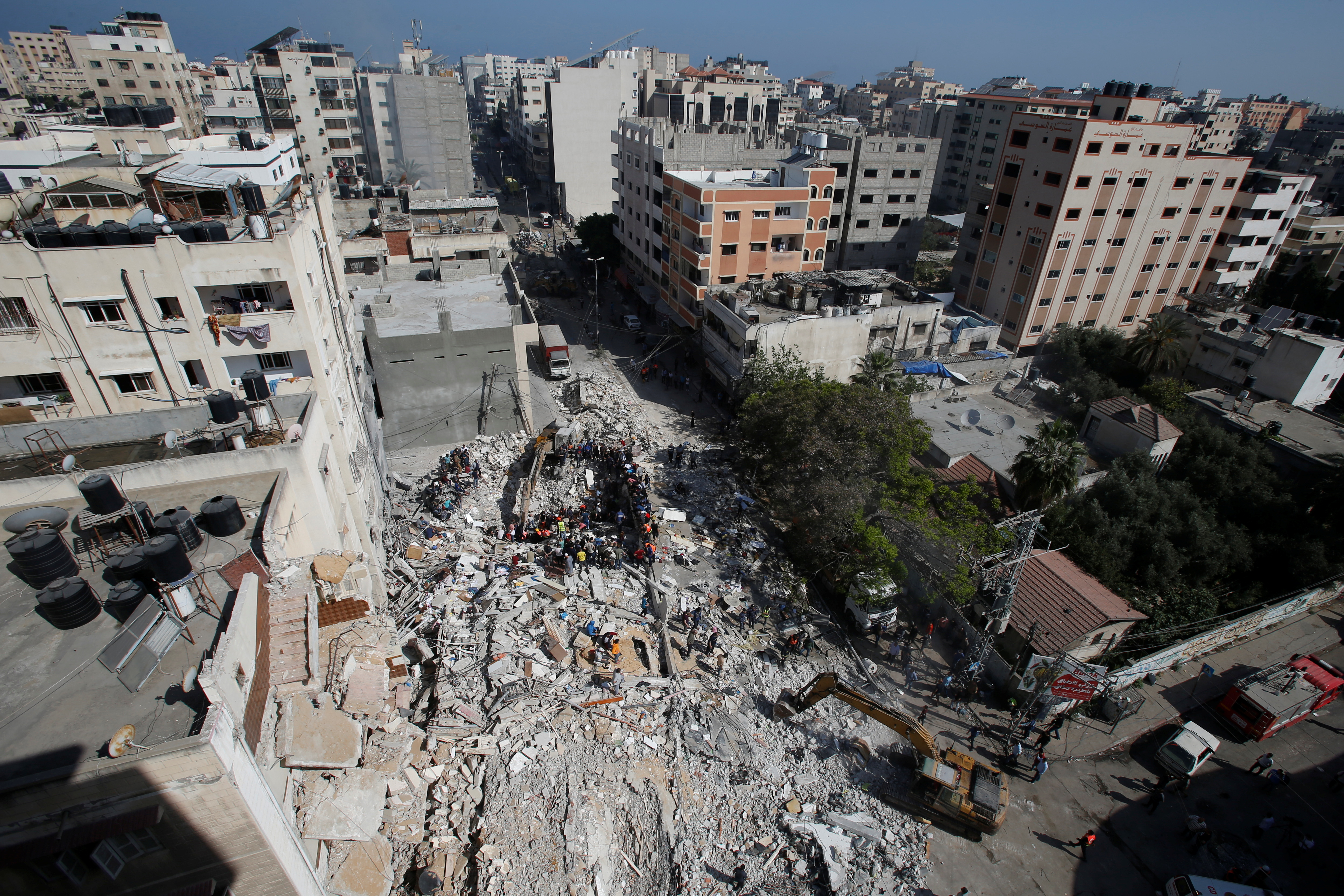 Rescuers search for people in the rubble of a building at the site of Israeli air strikes, in Gaza City May 16, 2021. REUTERS/Mohammed Salem