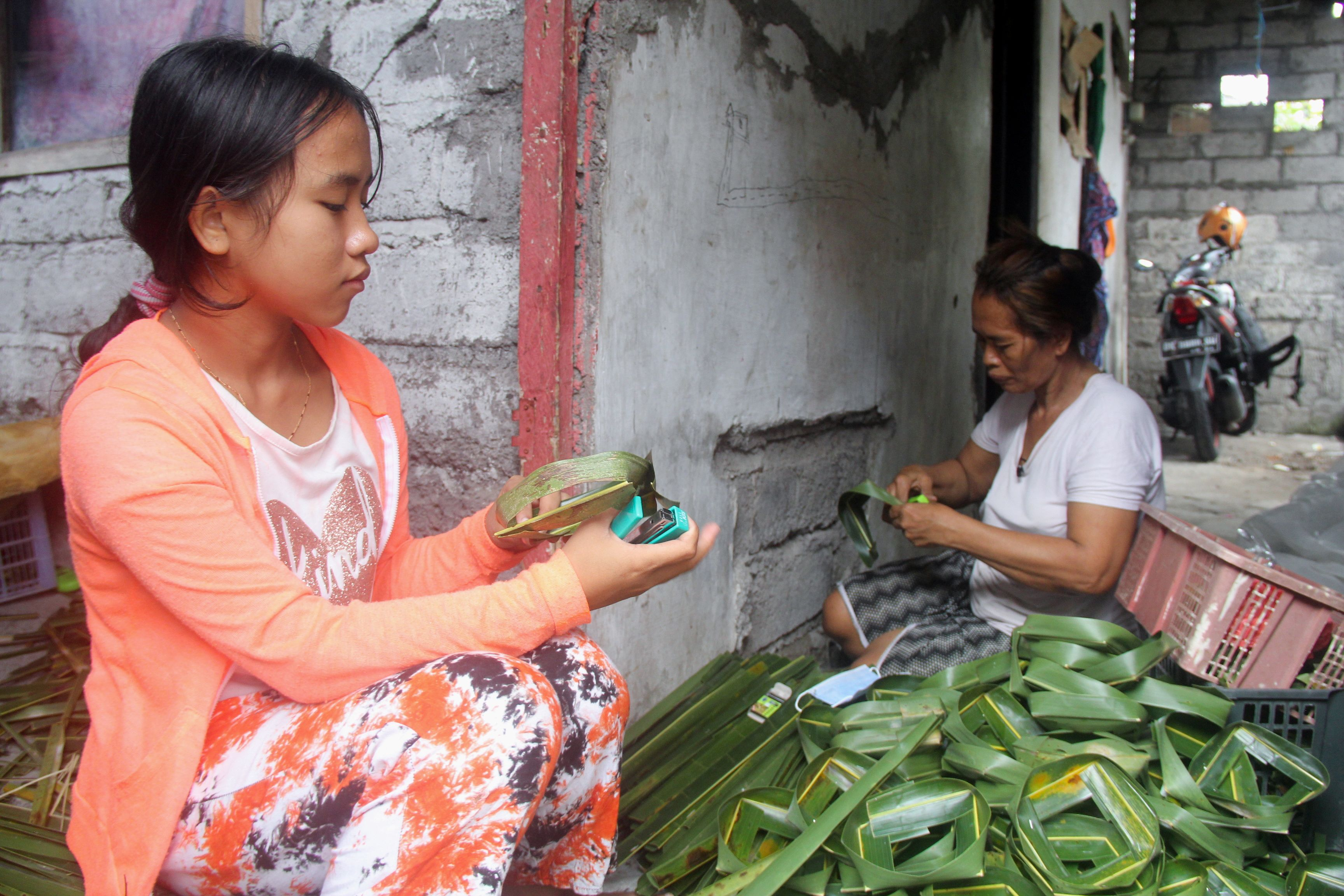 Ni Luh Nael, 13-years-old, helps her grandmother after dropping out of school during the coronavirus disease (COVID-19) pandemic in Denpasar, Bali, Indonesia, September 11, 2021. Picture taken September 11, 2021. REUTERS/Wayan Sukarda  NO RESALES. NO ARCHIVES