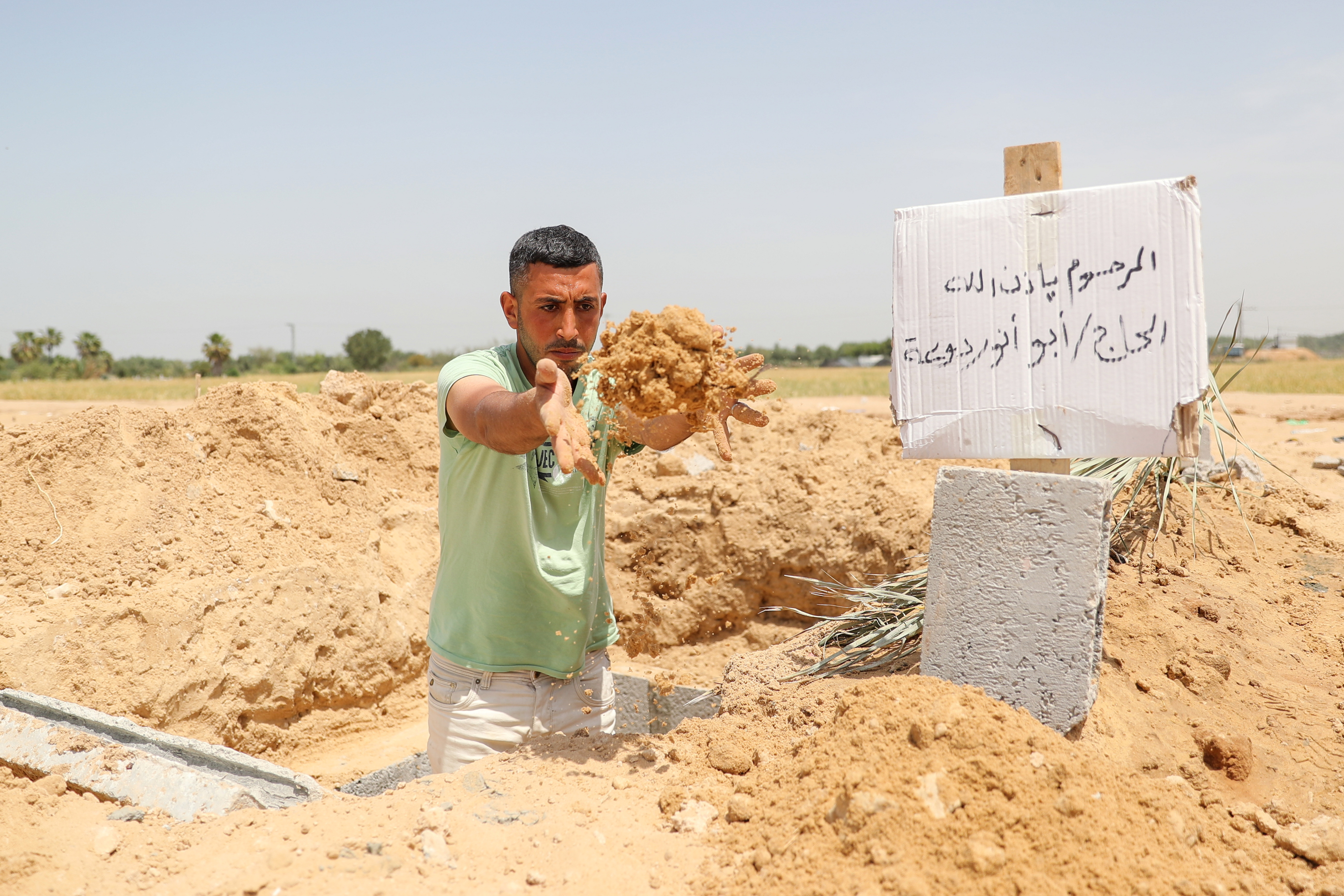 Palestinian worker Mohammad al-Haresh, 30, digs a grave for a coronavirus disease (COVID-19) victim, at a cemetery, east of Gaza City April 20, 2021. Picture taken April 20, 2021. REUTERS/Mohammed Salem