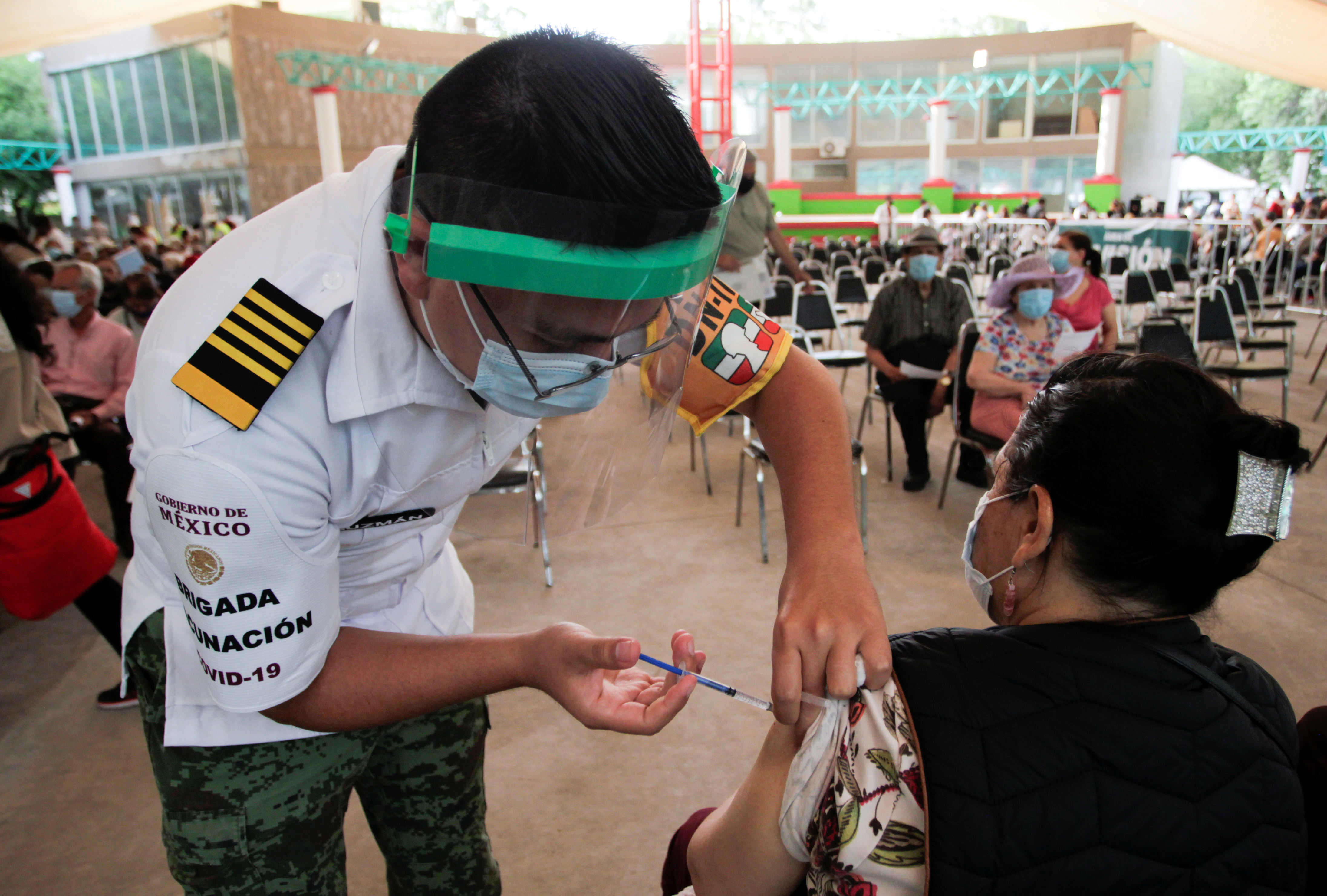 A woman receives a dose of the AstraZeneca coronavirus disease (COVID-19) vaccine, during a mass vaccination program in Monterrey, Mexico April 12, 2021. REUTERS/Daniel Becerril