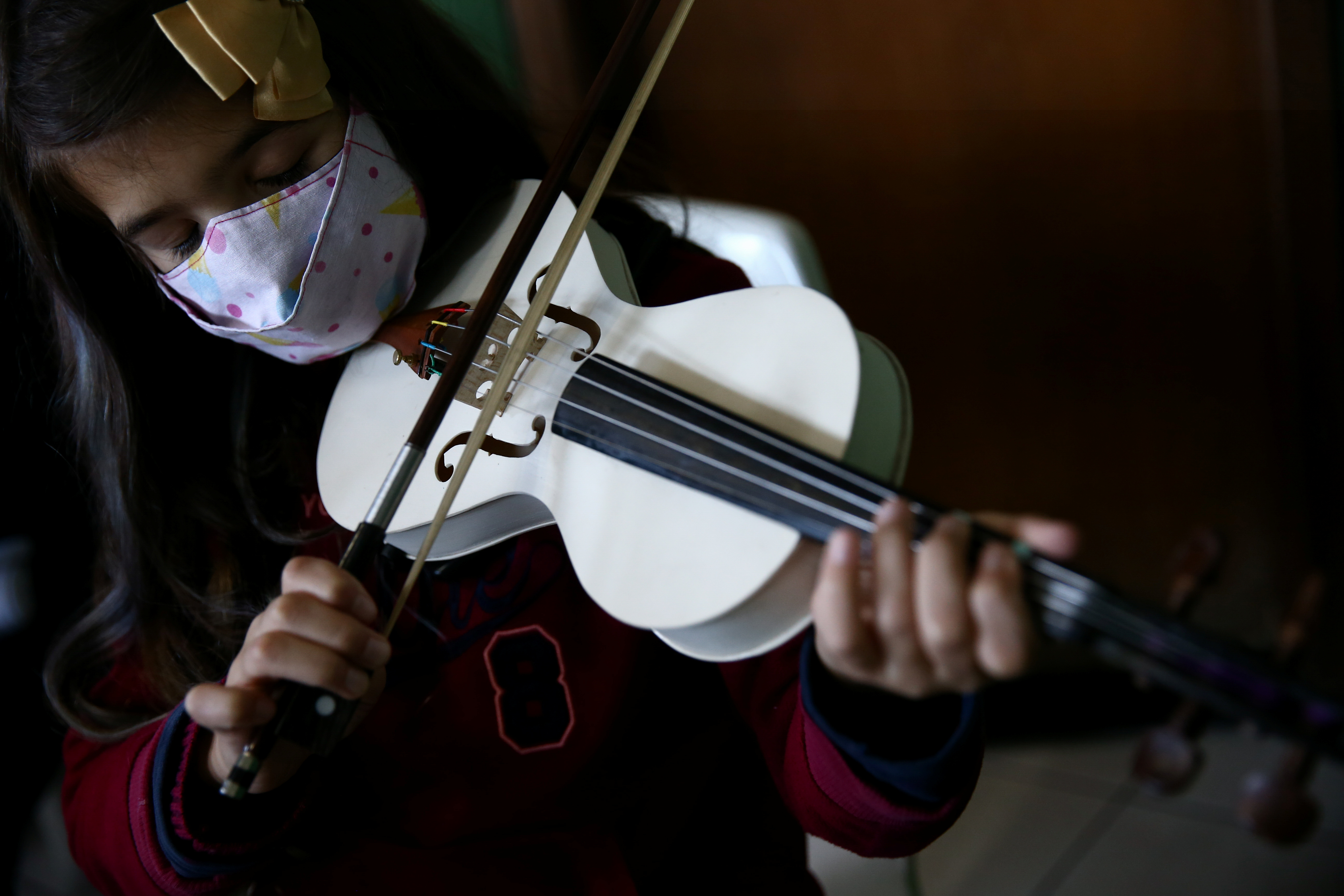 A student plays a violin made from PVC piping at Locomotiva Project, a free music school for at-risk children in Santo Andre, Brazil August 4, 2021. REUTERS/Carla Carniel