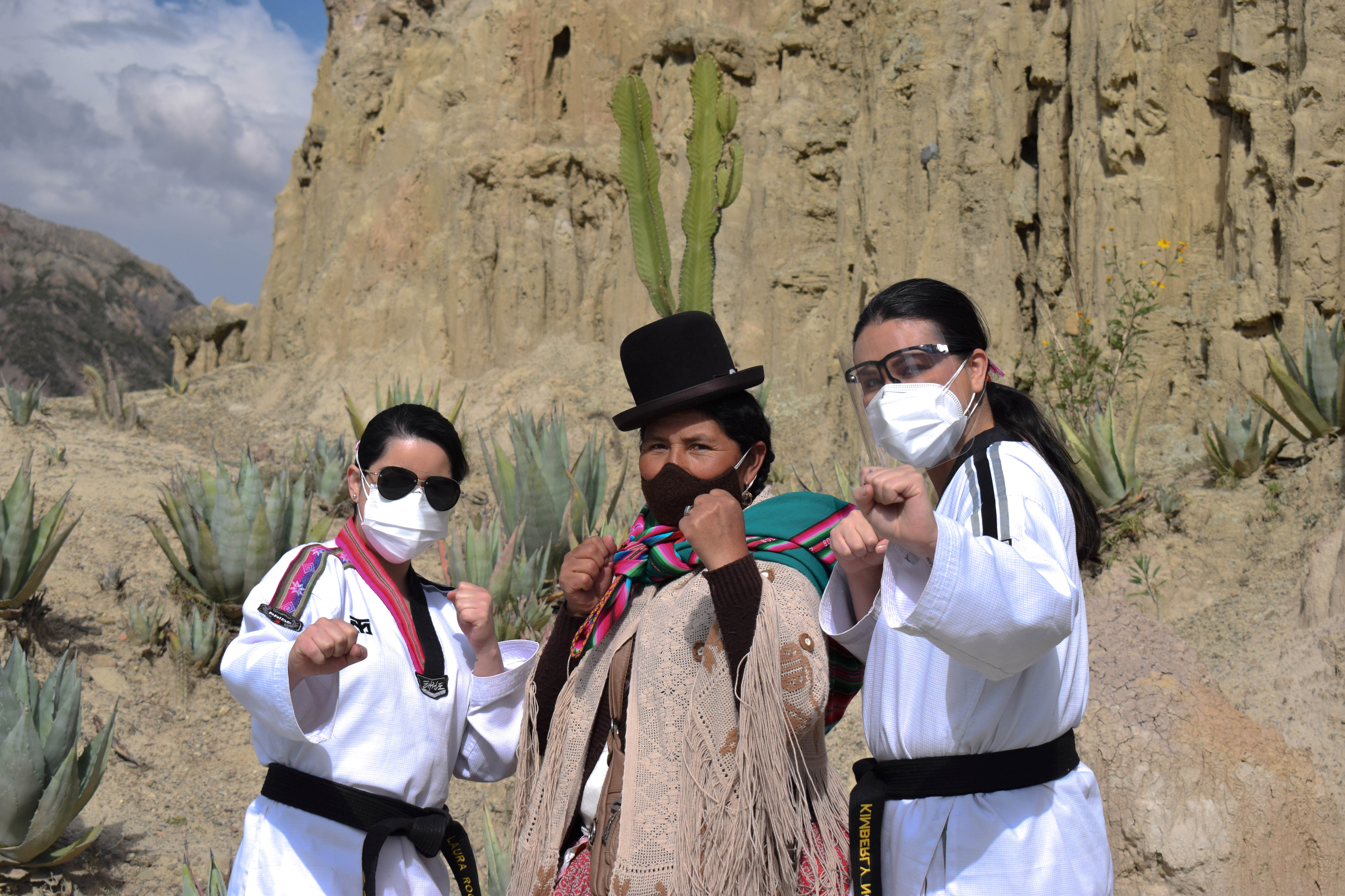 A Bolivian Aymara woman poses for a photograph with Sports Psychologist Laura Roca (L) and Personal Development and Women's coach Kimberly Nosa (R) of the Warmi Power social project during a taekwondo class to learn self-defence, on the outskirts of La Paz, Bolivia April 23, 2021. Picture taken April 23, 2021. Laura Roca/Warmi Power/Handout via REUTERS