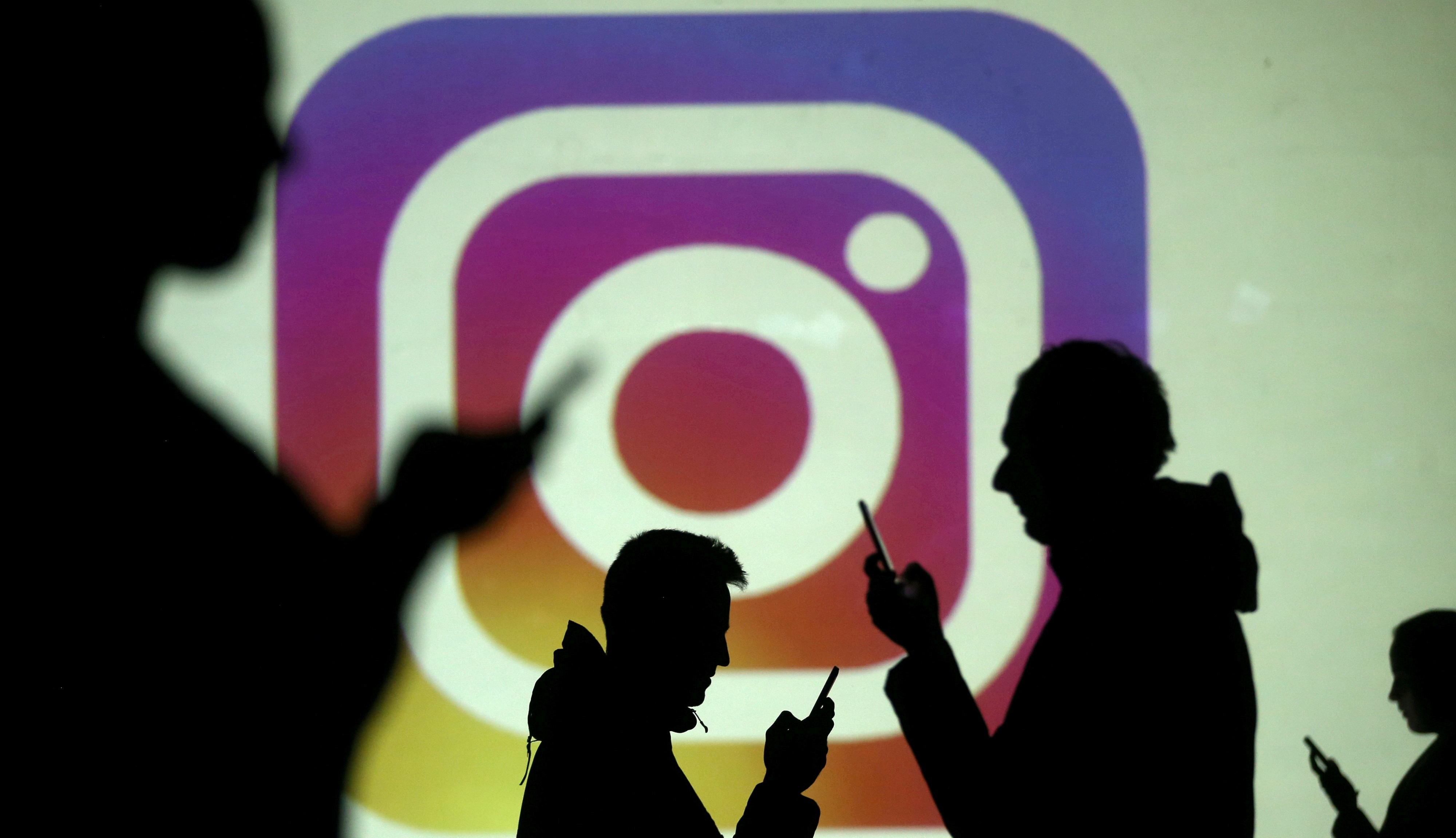 Silhouettes of mobile users are seen next to a screen projection of the Instagram logo in this picture illustration taken March 28, 2018.  REUTERS/Dado Ruvic/Illustration