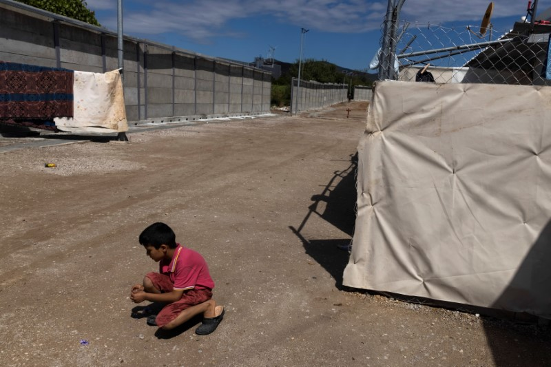 A boy plays next to a newly built concrete wall inside the Ritsona camp for refugees and migrants, in Greece, June 15, 2021. REUTERS/Alkis Konstantinidis