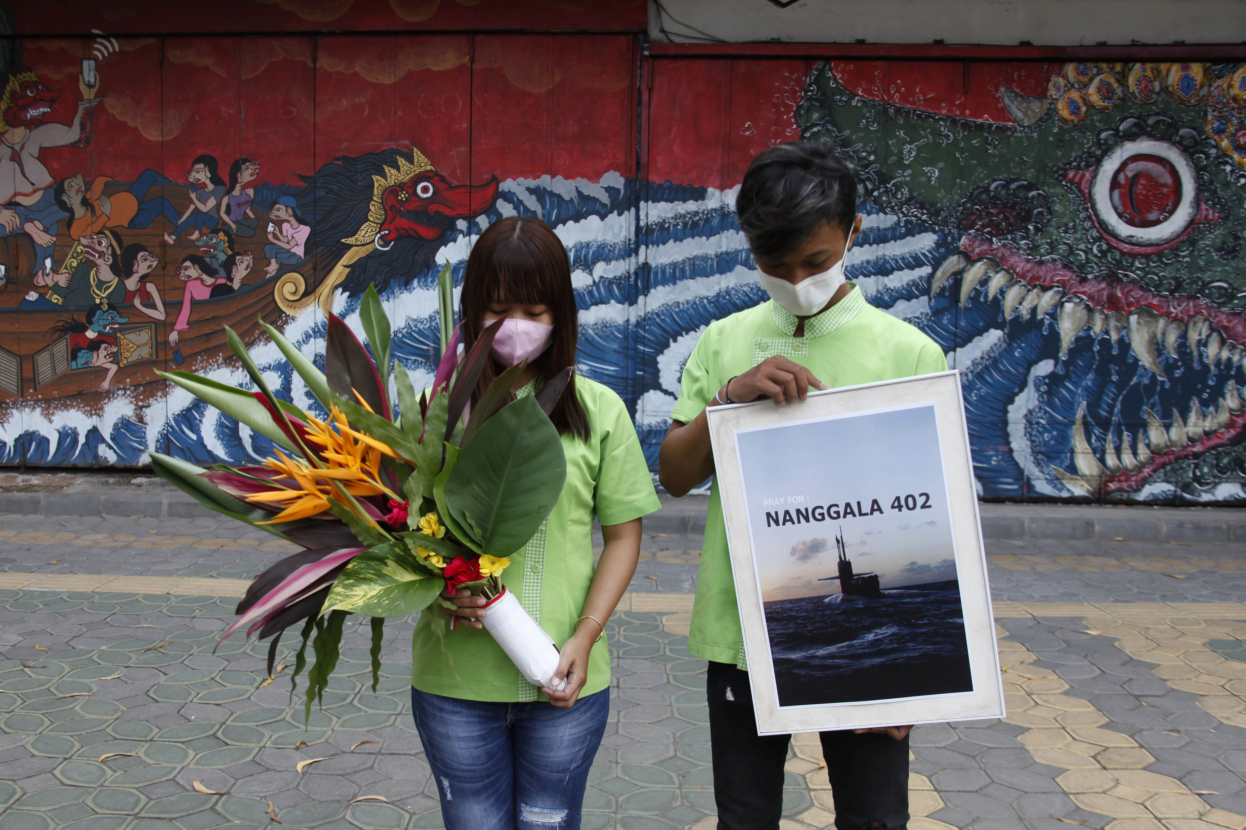 People holding a placard and flowers bow as they pray for the crew of submarine KRI Nanggala-402 which has sunk at the north of Bali sea, during a vigil in Solo, Central Java province, Indonesia, April 25, 2021 in this photo taken by Antara Foto.  Antara Foto/Maulana Surya/ via REUTERS