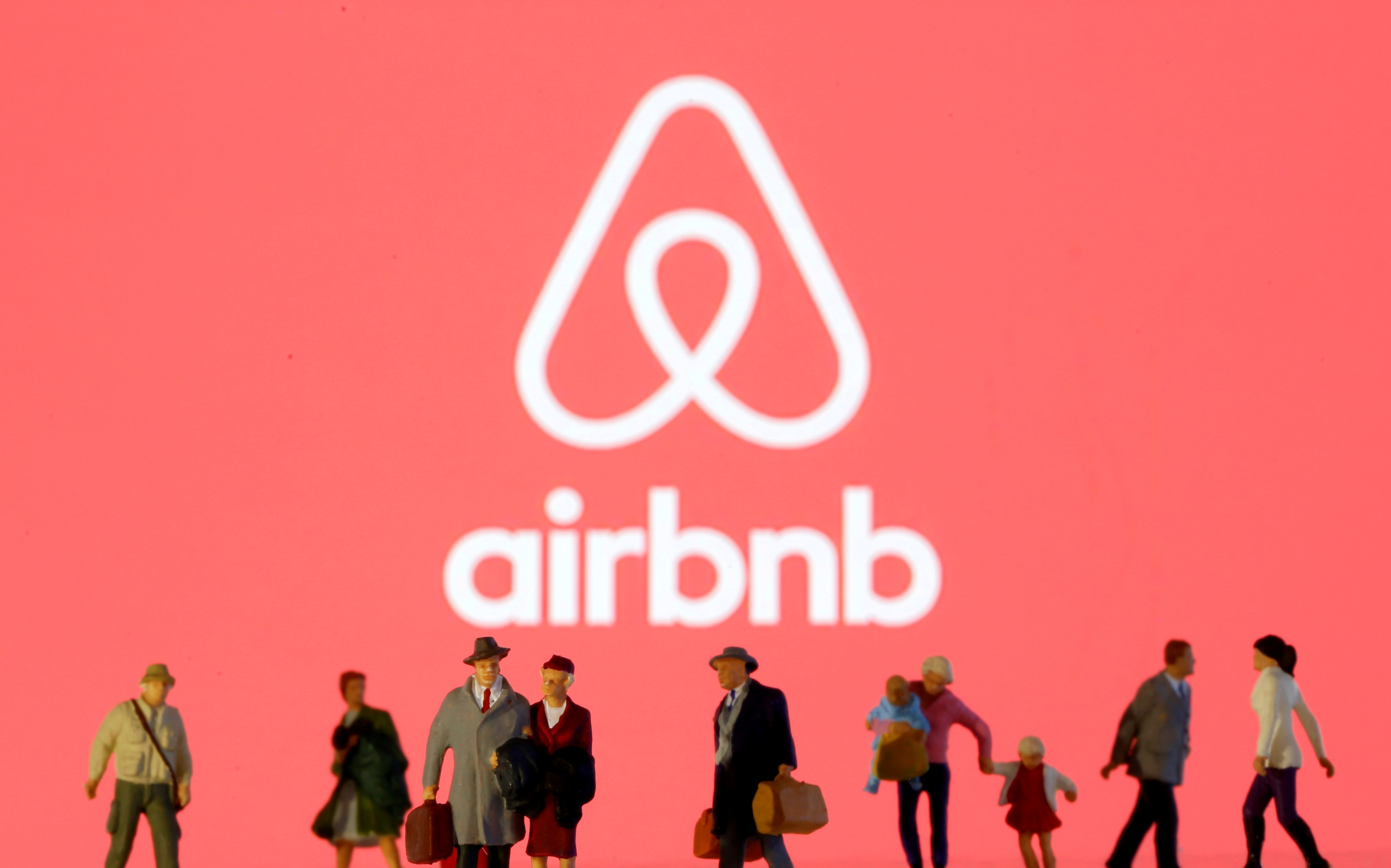 Small toy figures are seen in front of displayed Airbnb logo in this illustration taken March 19, 2020. REUTERS/Dado Ruvic/Illustration