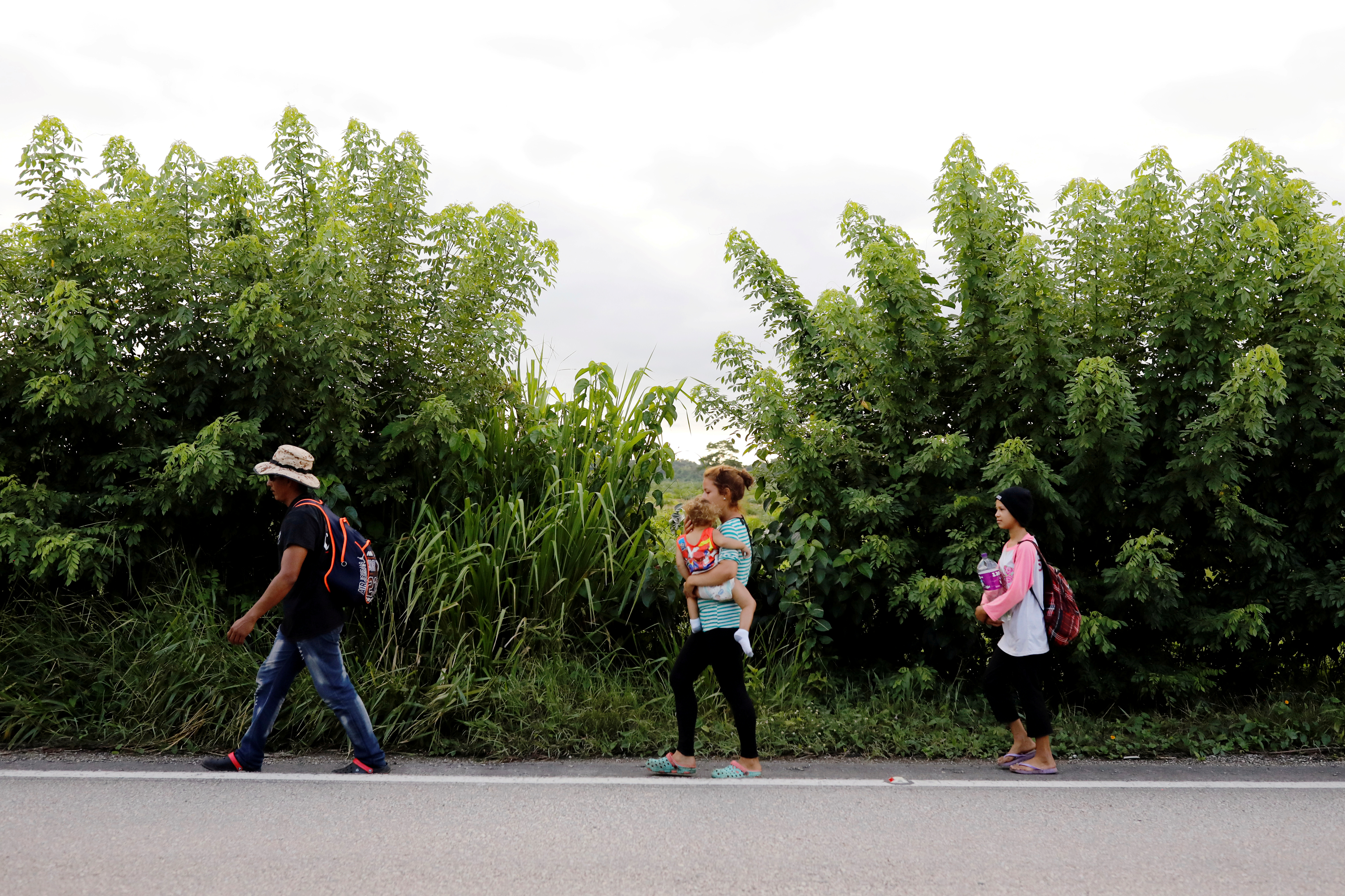 Honduran migrants trying to reach the U.S. walk along a road as they move towards the Mexico border, in San Pedro Cadenas, Guatemala October 3, 2020. REUTERS/Luis Echeverria/File Photo