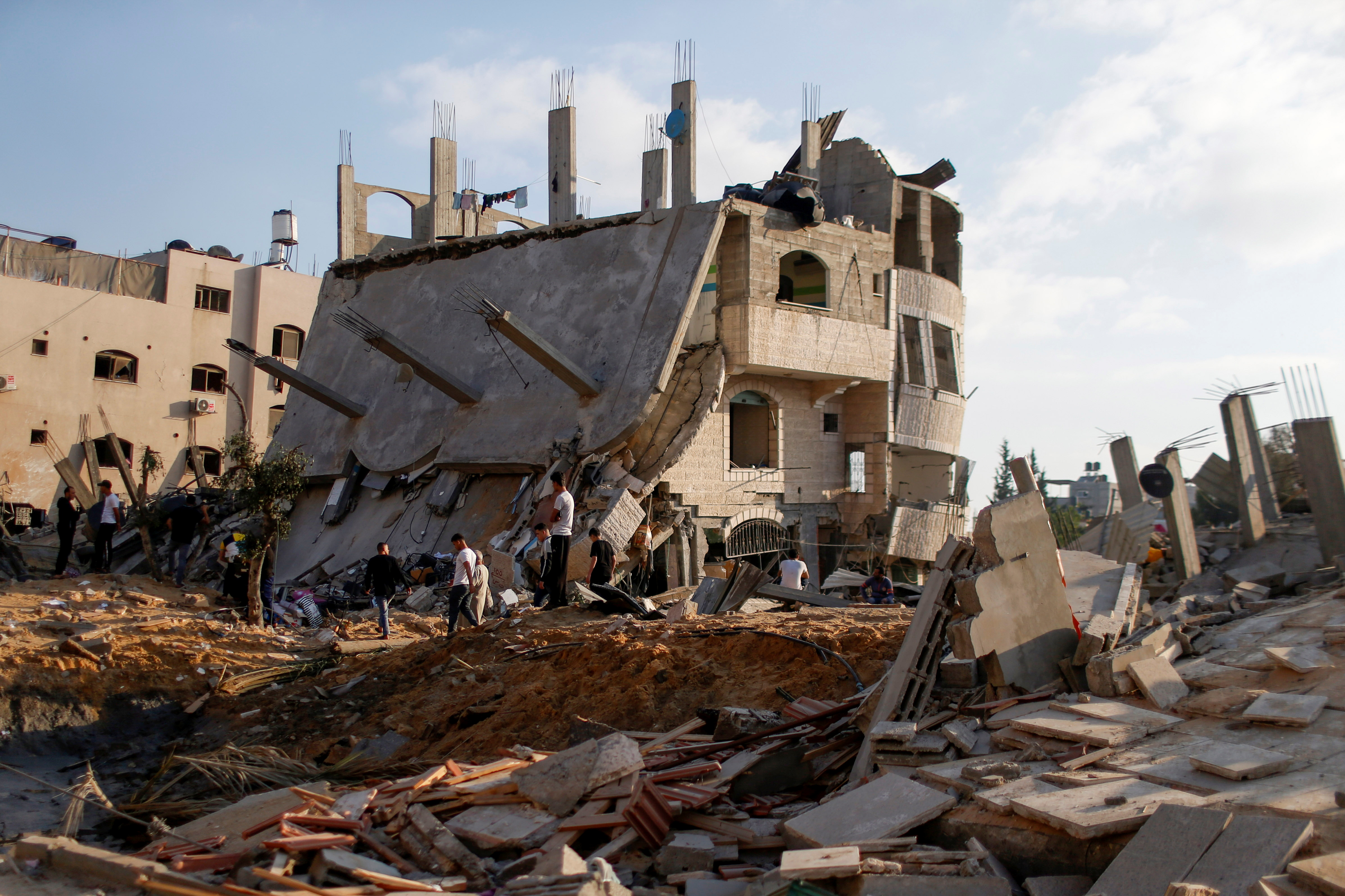 Palestinians gather around the ruins of buildings which were destroyed in Israeli air strikes amid a flare-up of Israeli-Palestinian violence, in the northern Gaza Strip May 13, 2021. REUTERS/Mohammed Salem