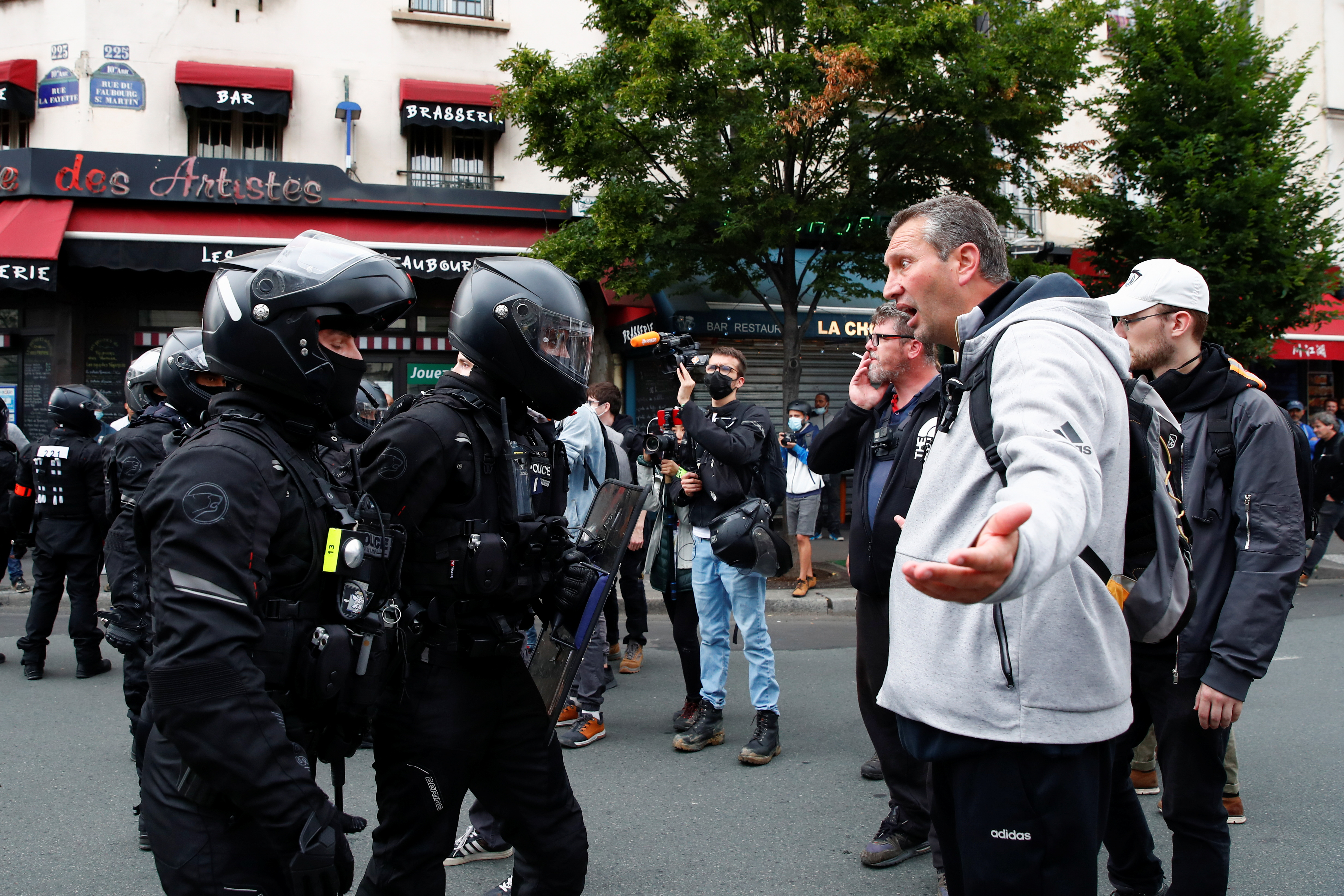 A demonstrator argues with police officers during a protest against the new measures announced by French President Emmanuel Macron to fight the coronavirus disease (COVID-19) outbreak, in Paris, France, July 14, 2021. REUTERS/Gonzalo Fuentes