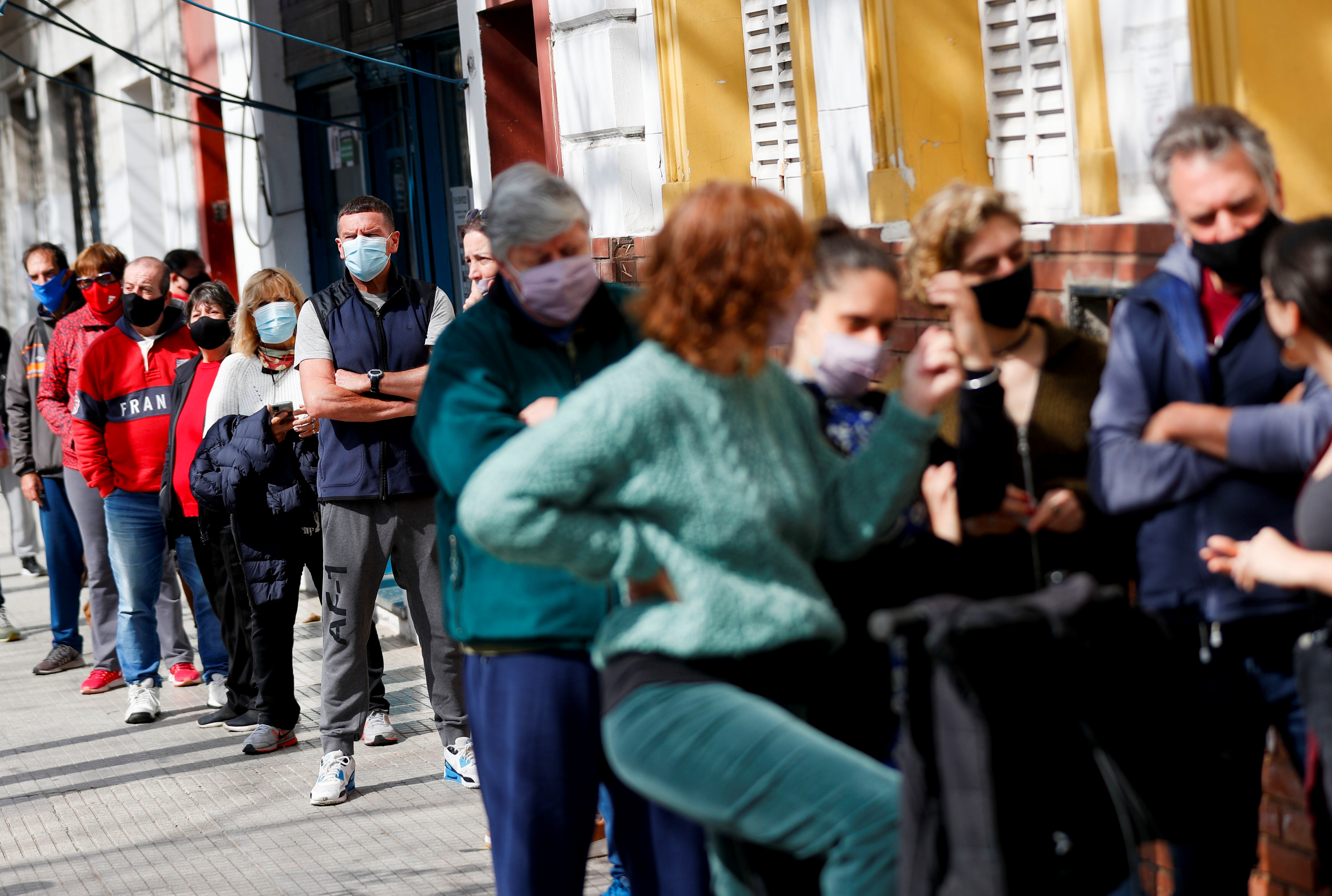 People queue outside a polling station before casting their vote during primary legislative elections, in Buenos Aires, Argentina September 12, 2021. REUTERS/Agustin Marcarian
