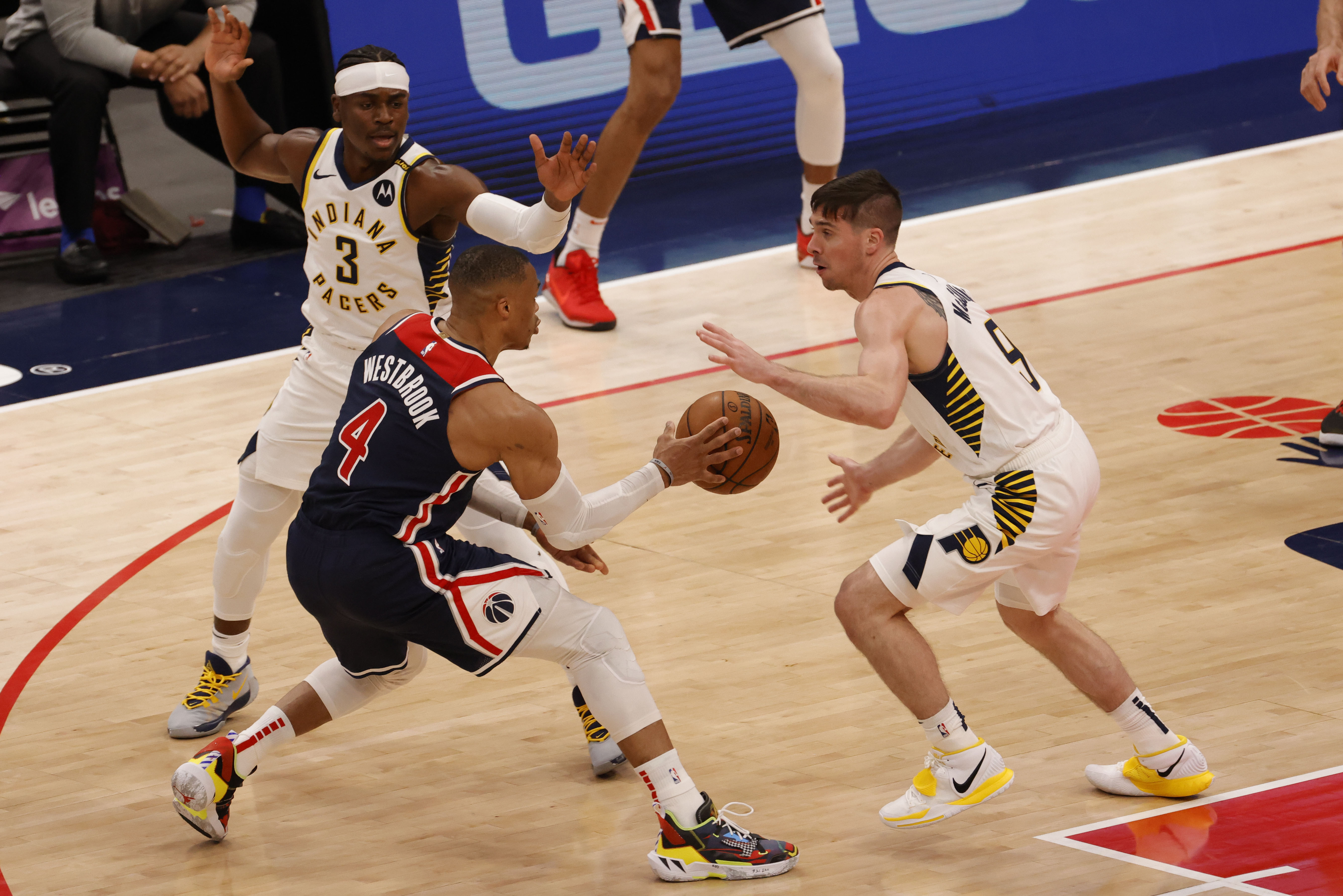 May 3, 2021; Washington, District of Columbia, USA; Washington Wizards guard Russell Westbrook (4) passes the ball as Indiana Pacers guard Aaron Holiday (3) and Pacers guard T.J. McConnell (9) defend in the third quarter at Capital One Arena. Mandatory Credit: Geoff Burke-USA TODAY Sports