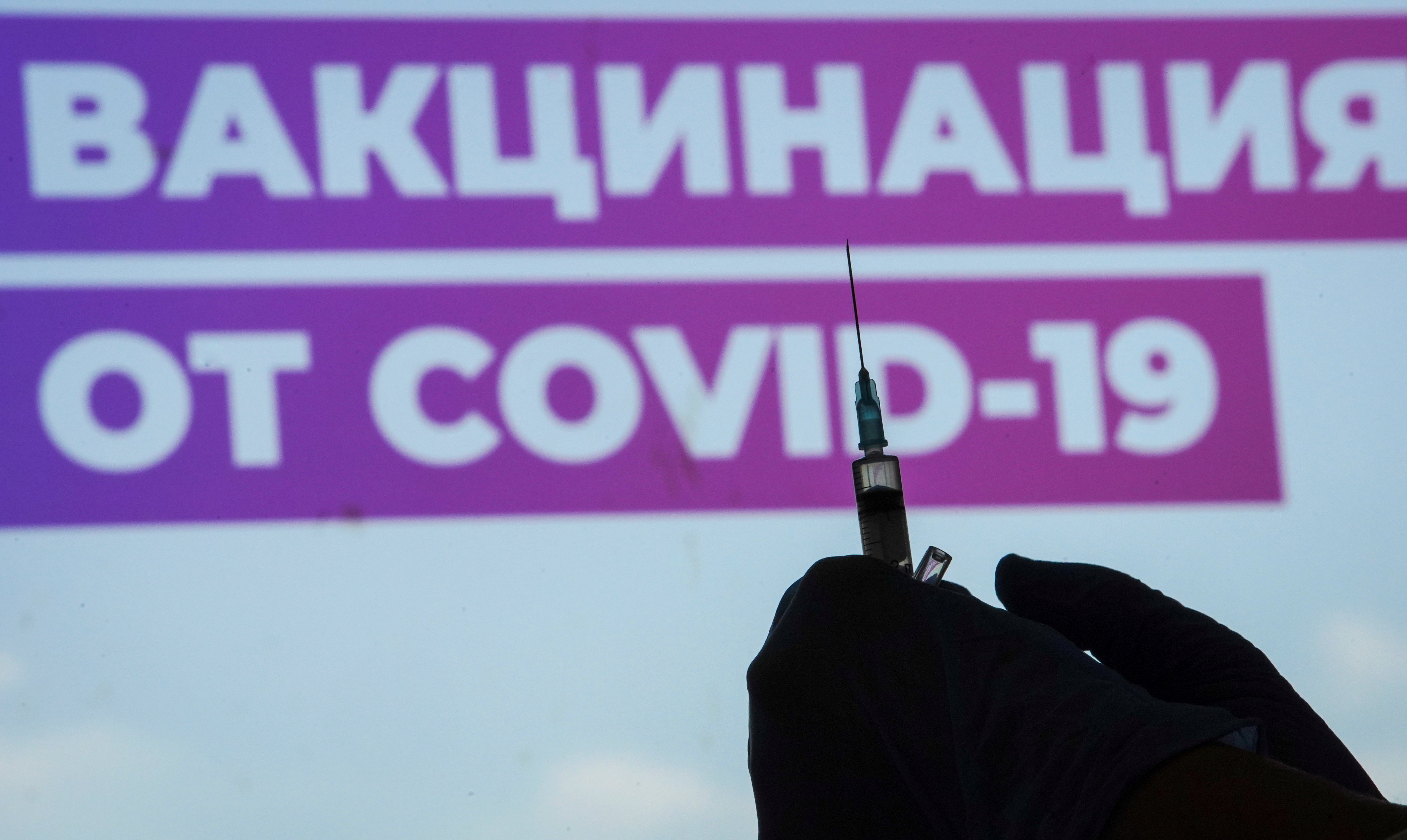 A healthcare worker prepares a one-dose Sputnik Light vaccine against the coronavirus disease (COVID-19) at a vaccination centre in Luzhniki Stadium in Moscow, Russia July 8, 2021. A sign reads Vaccination against COVID-19.  REUTERS/Tatyana Makeyeva