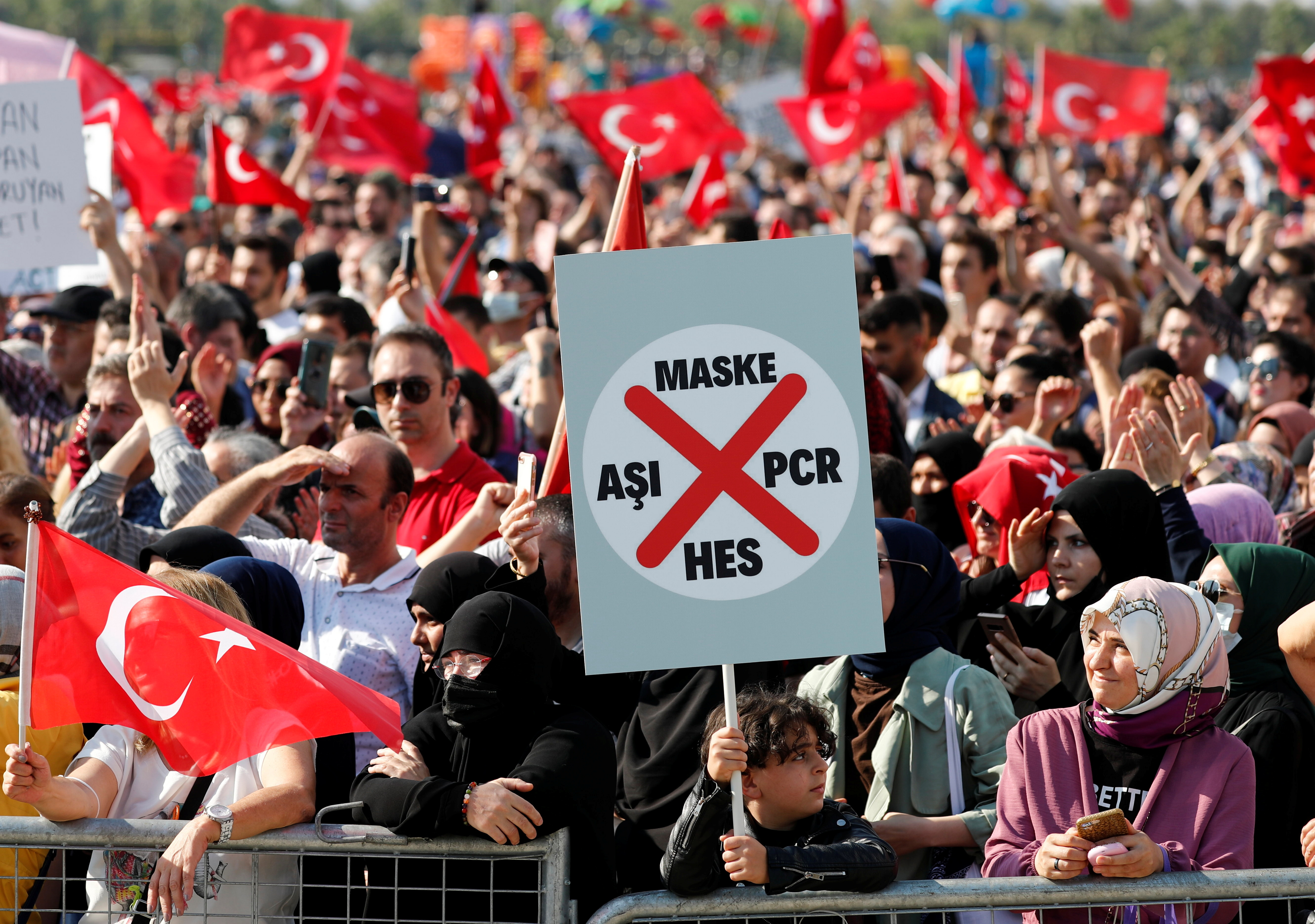 A boy holds a placard as anti-vaccine demonstrators wave Turkish flags during a protest against official coronavirus disease (COVID-19)-related mandates, including vaccinations, tests and masks, in Istanbul, Turkey September 11, 2021. REUTERS/Murad Sezer