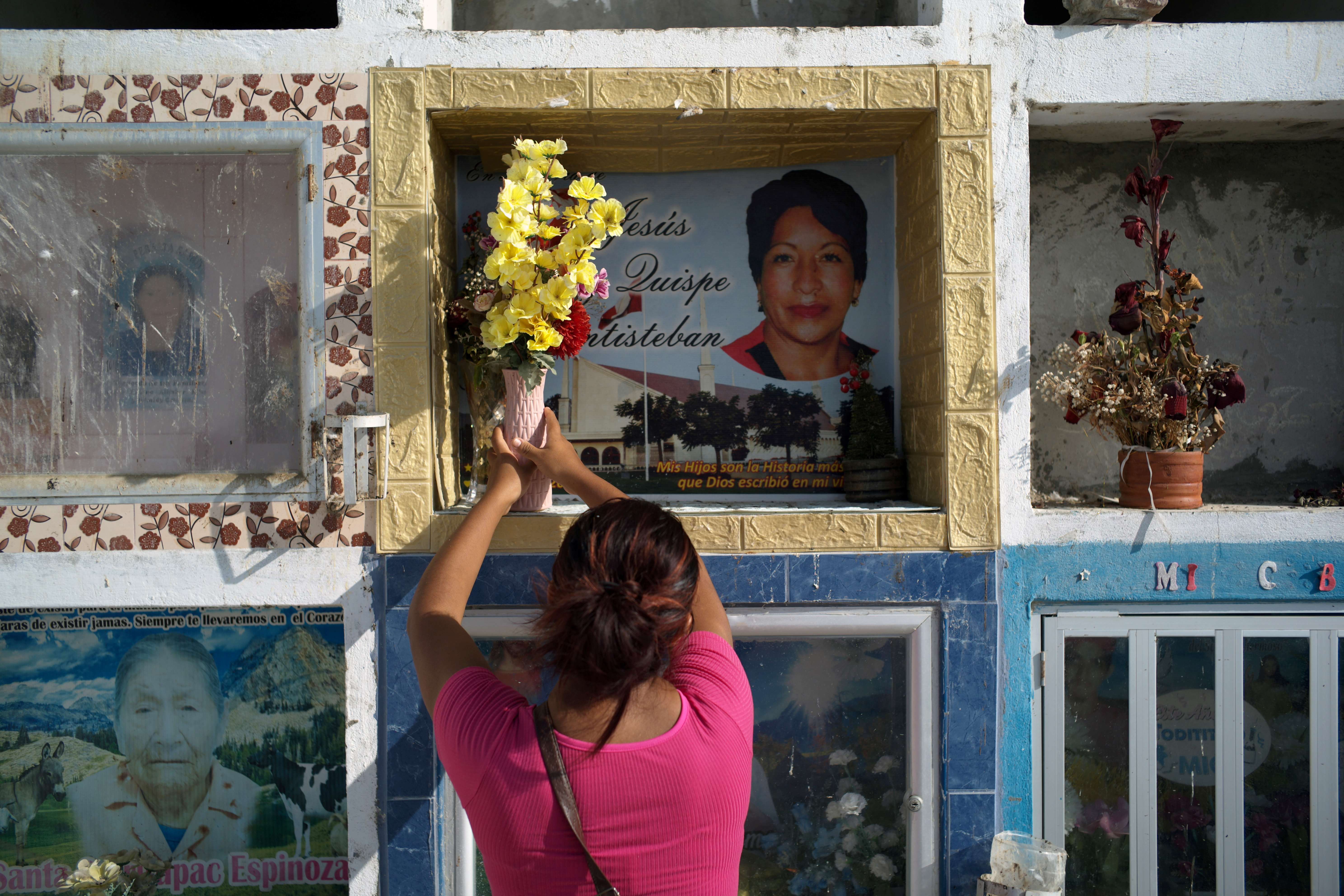 Hellen Nanez, who lost 13 relatives to the coronavirus disease (COVID-19) and whose father is being treated for COVID-19 in the Intensive Care Unit, visits the grave of her aunt, who died in June 2020 of COVID-19, in Pisco, Peru, May 9, 2021. Picture taken May 9, 2021. REUTERS/Alessandro Cinque - RC28CN9DIM91