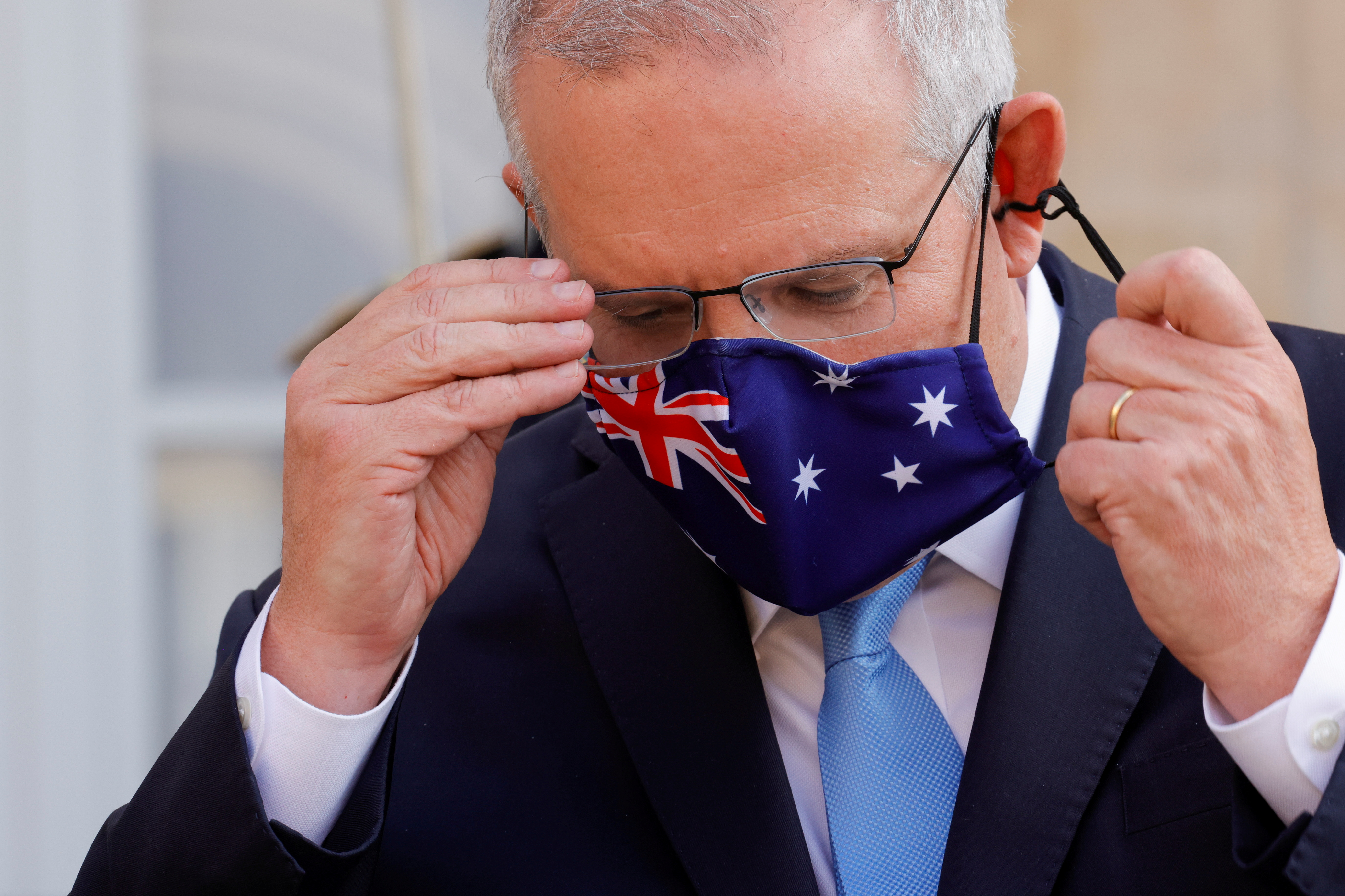Australian Prime Minister Scott Morrison adjusts his mask during a news conference he holds with French President Emmanuel Macron in front of the Elysee Palace in Paris, France, June 15, 2021. REUTERS/Pascal Rossignol